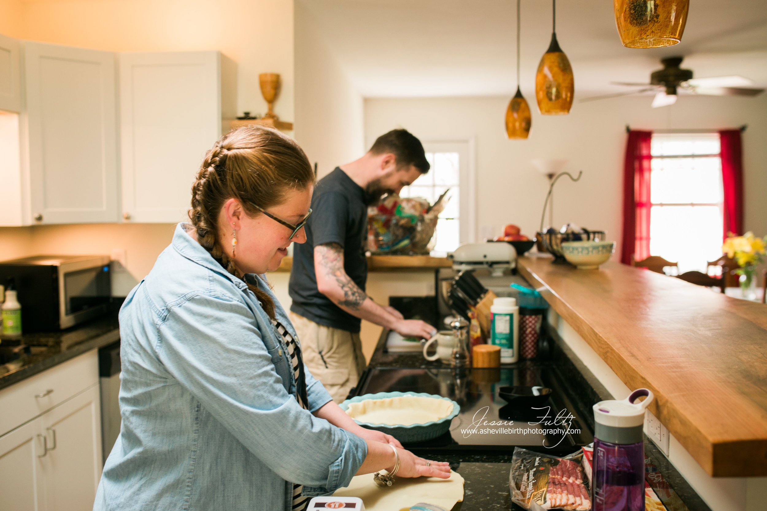 red-headed pregnant woman and husband making pie crusts in kitchen