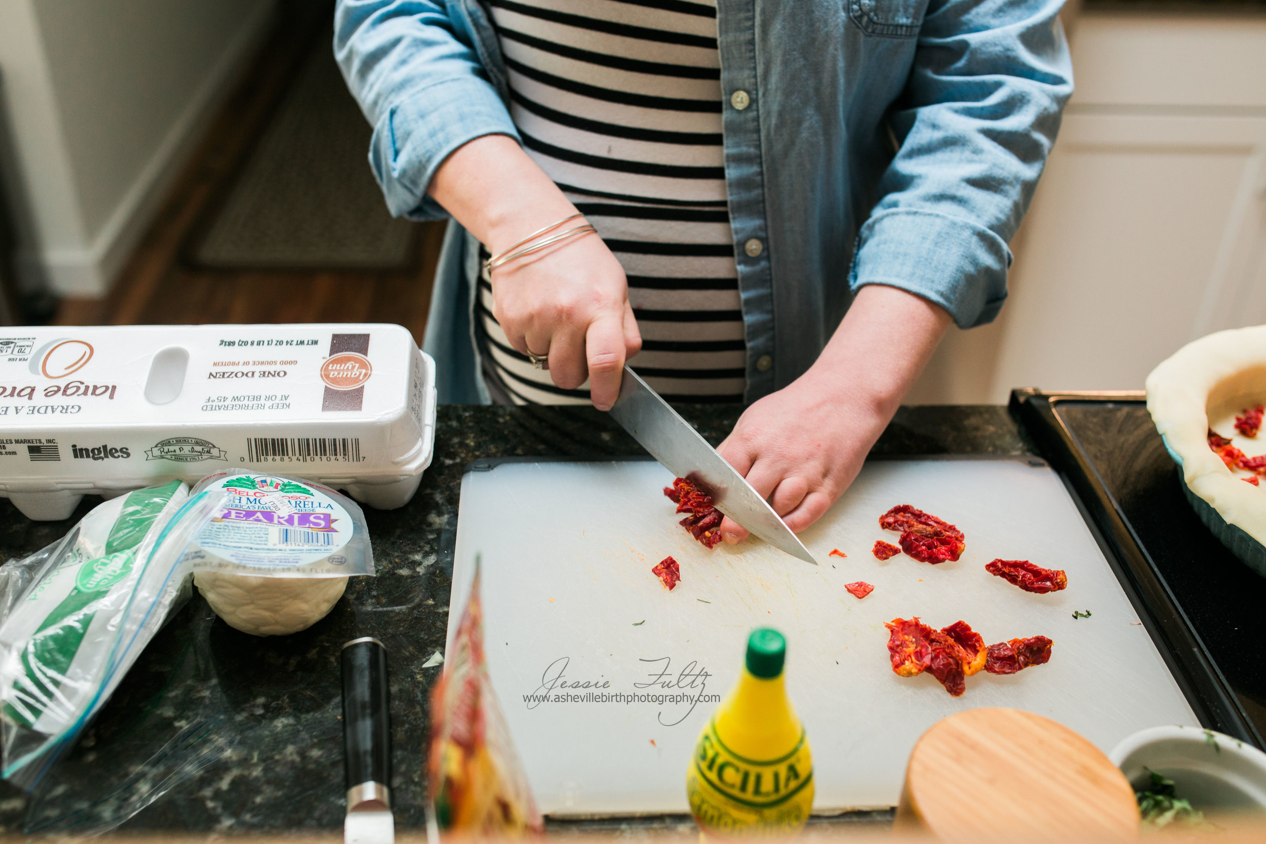 close-up picture of a pregnant woman chopping sun-dried tomatoes on a white cutting board