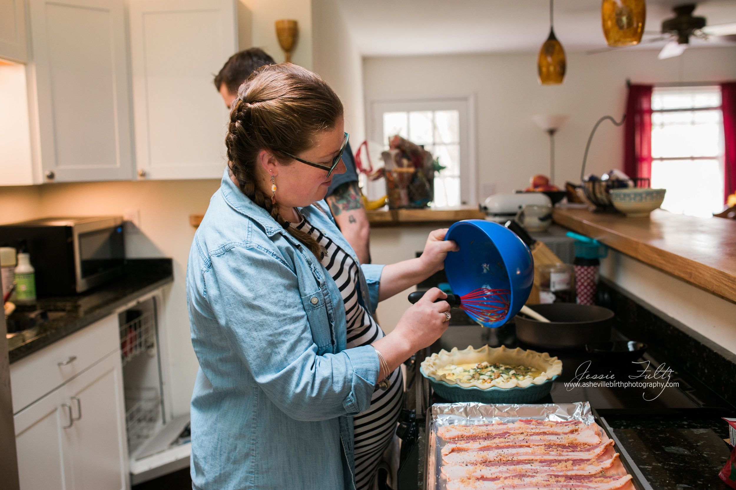 pregnant woman in striped dress pouring quiche mixture from a a blue bowl using a red whisk