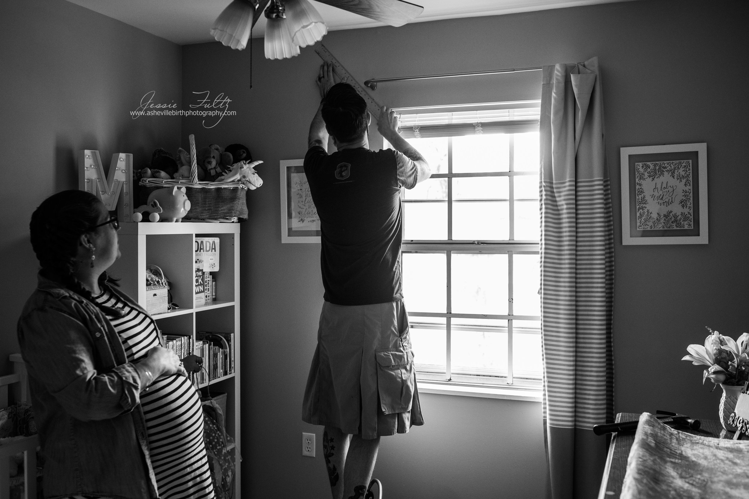 black and white picture of a pregnant woman holding her belly and watching her husband who is wearing a kilt measure the wall in their nursery