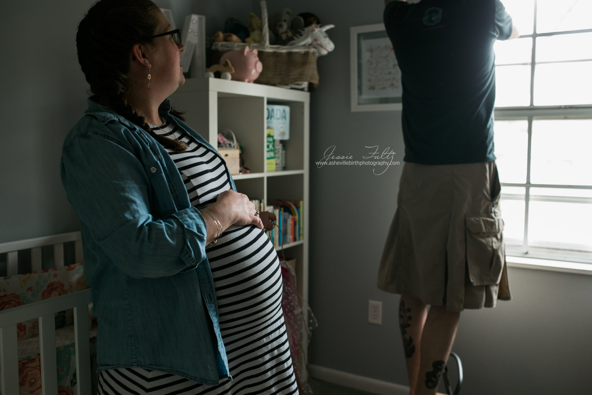 profile of a pregnant woman in a striped dress holding her belly and leaning on her baby's crib