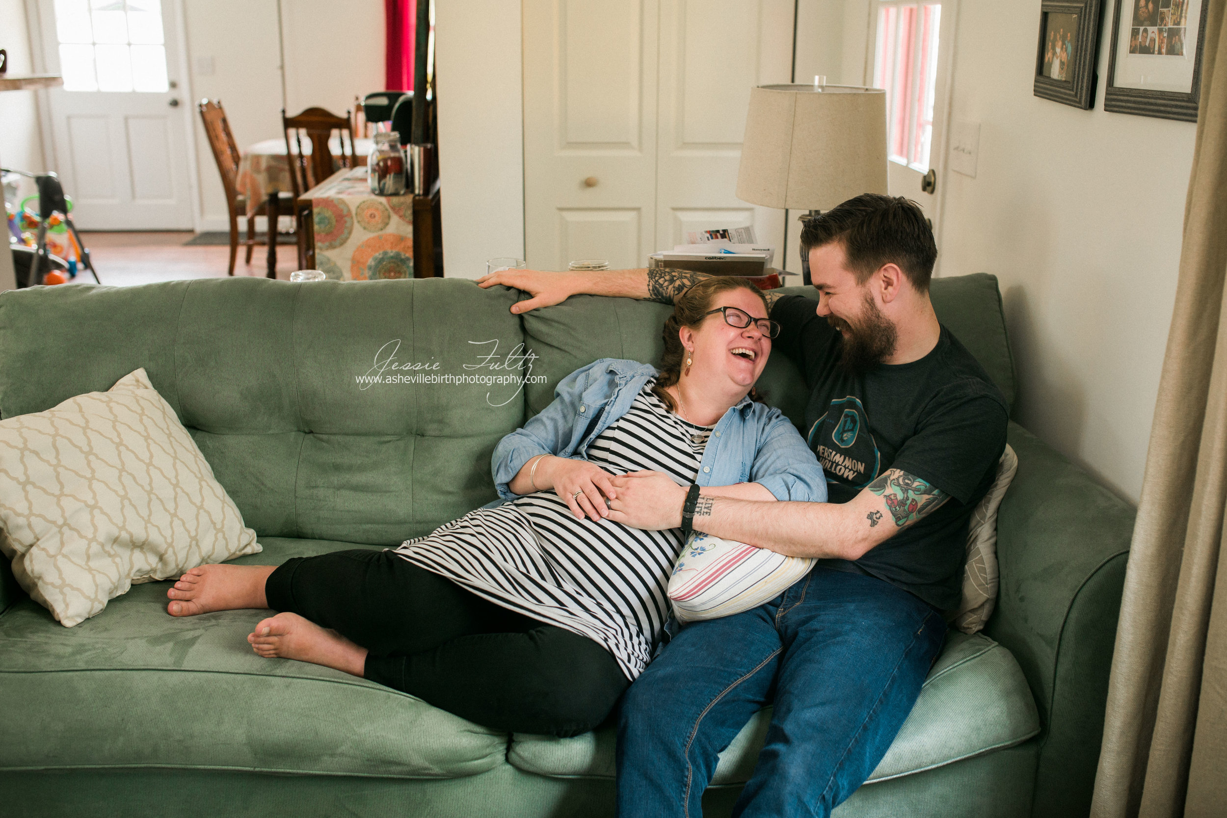 pregnant woman in striped dress and husband cuddling up on the couch and laughing