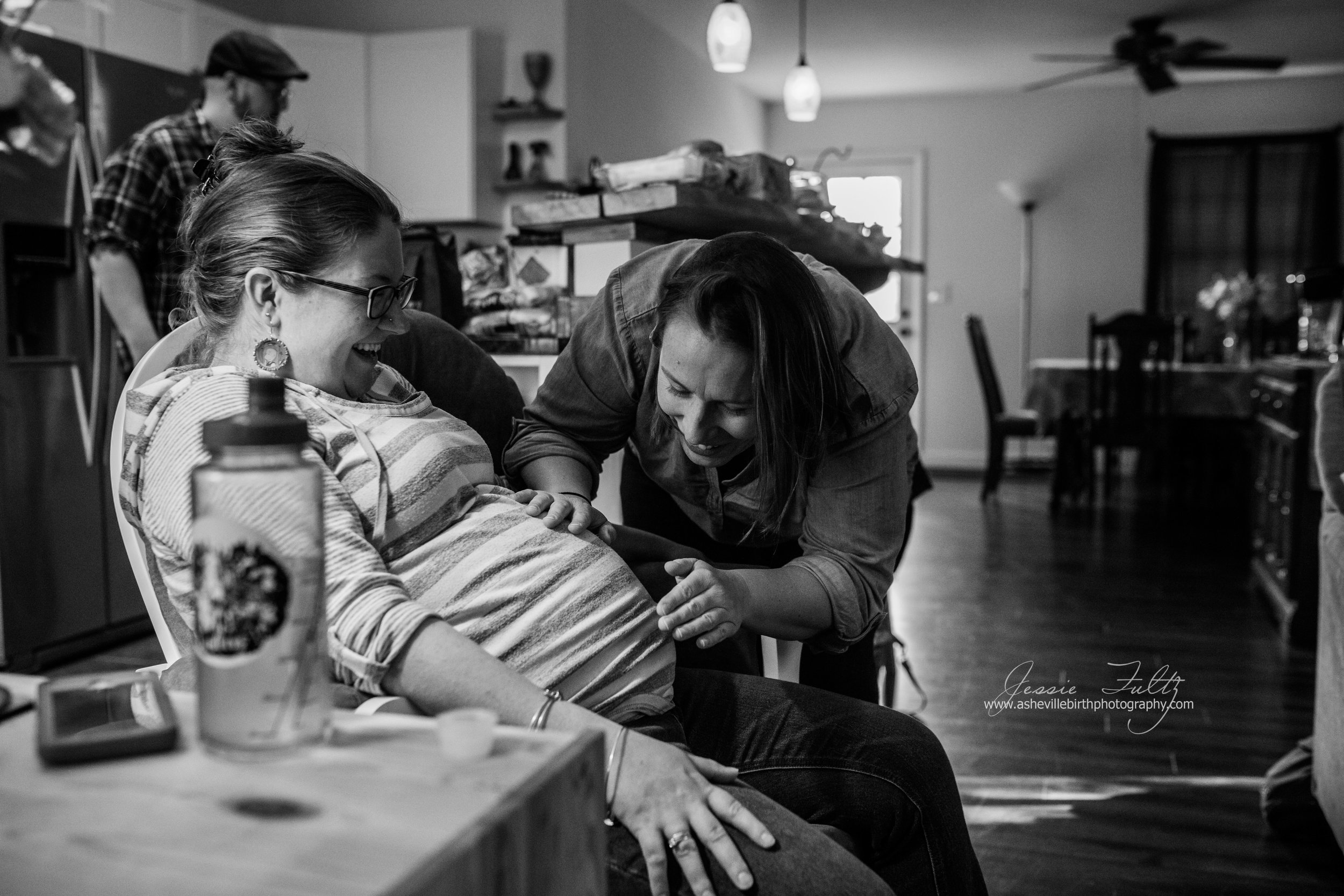 black and white photo of a woman talking to her friend's pregnant belly