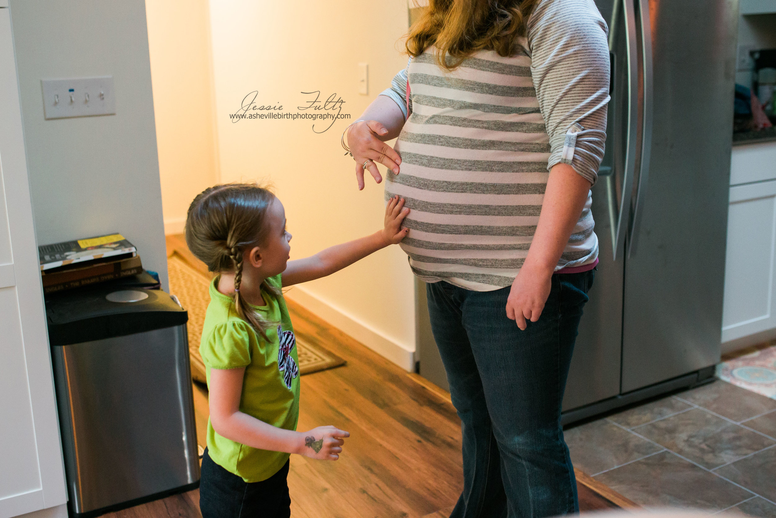 a young girl in a green shirt and pigtails touching a pregnant woman's belly