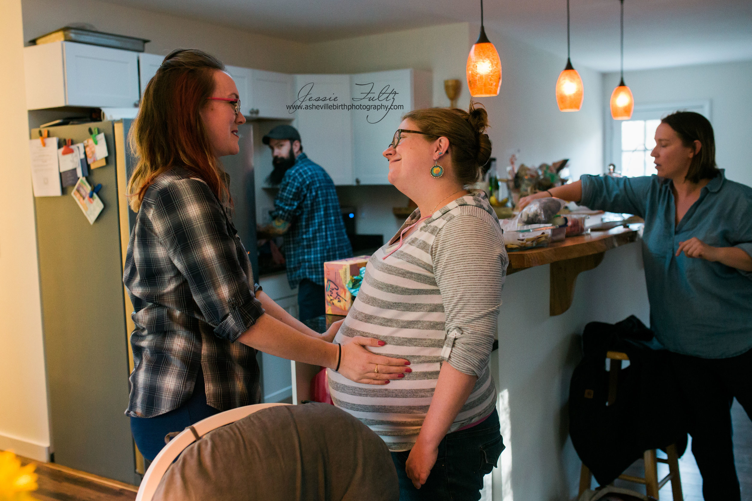 a woman holding her friend's pregnant belly and talking to her