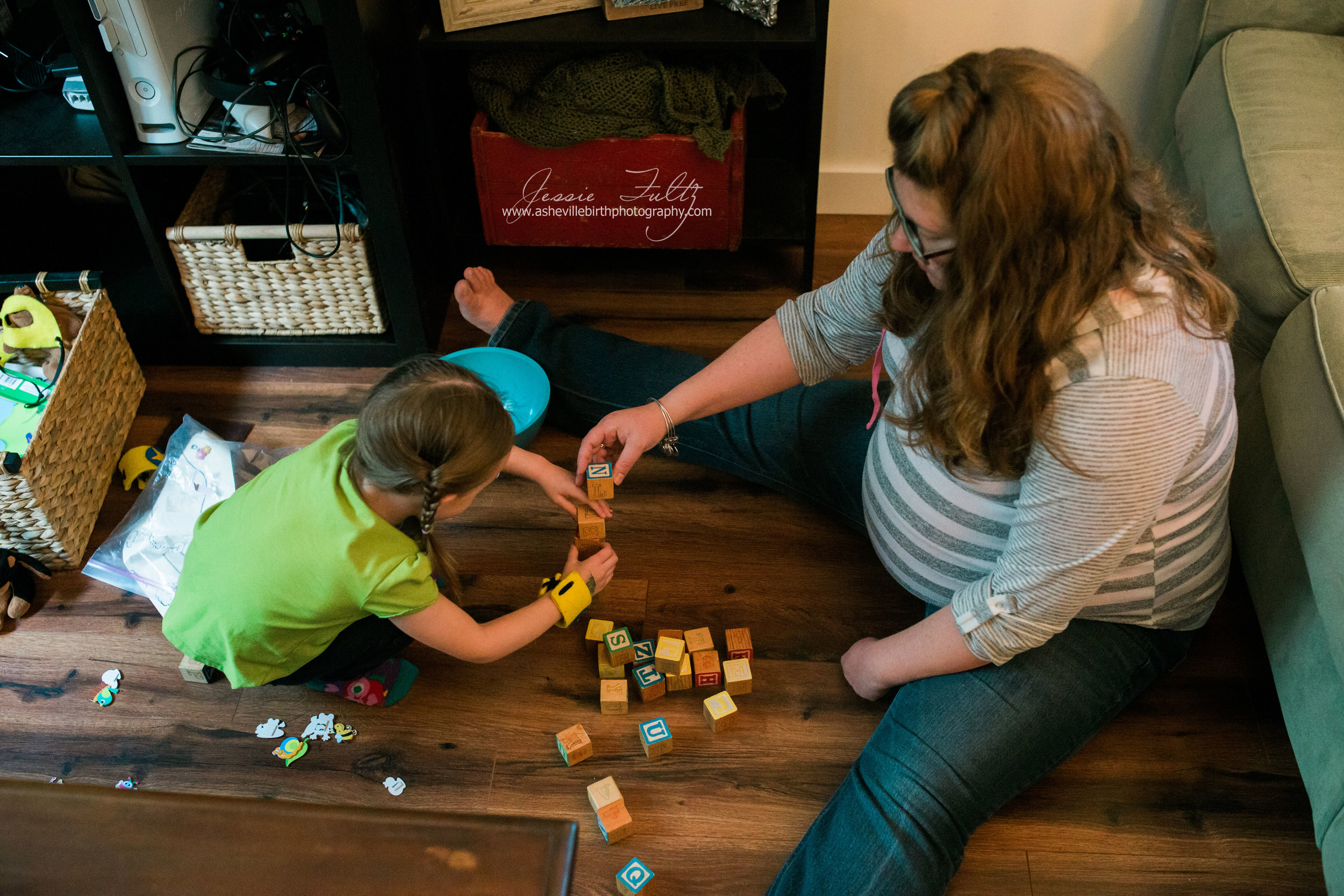 a pregnant woman and young girl using letter blocks to build a tower