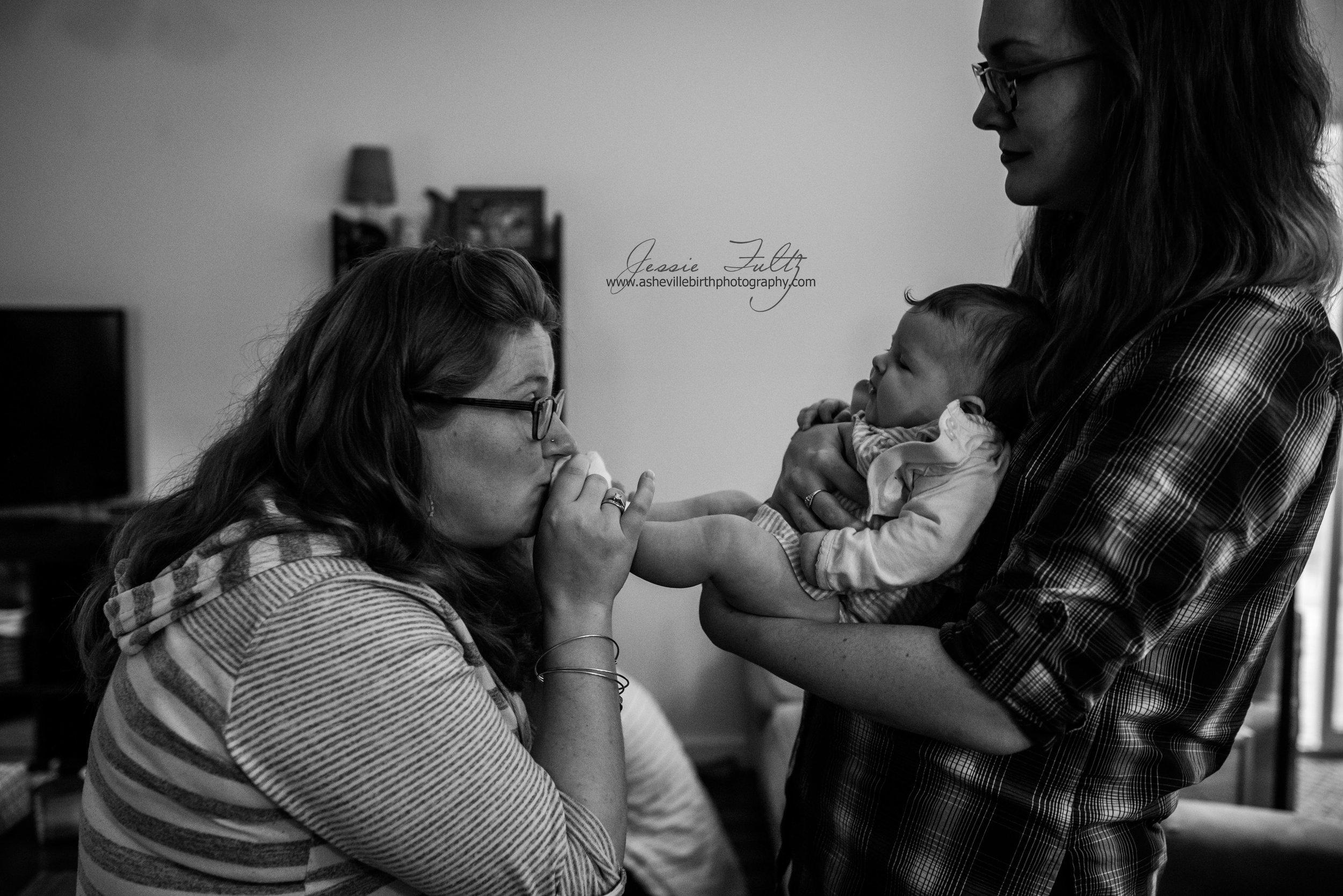 pregnant woman kissing an infant's feet