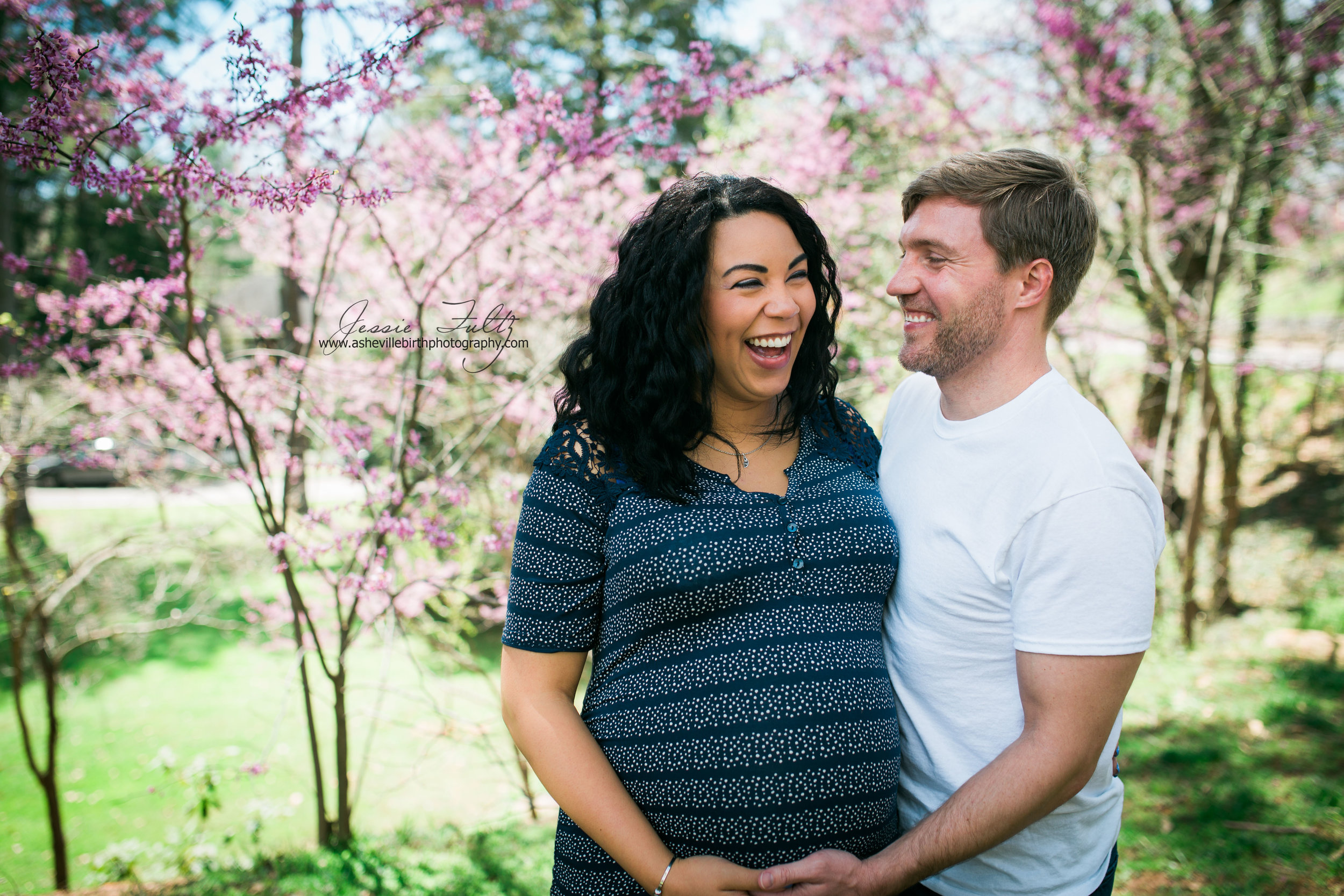 pregnant woman and her husband laughing while standing in front of cherry blossons