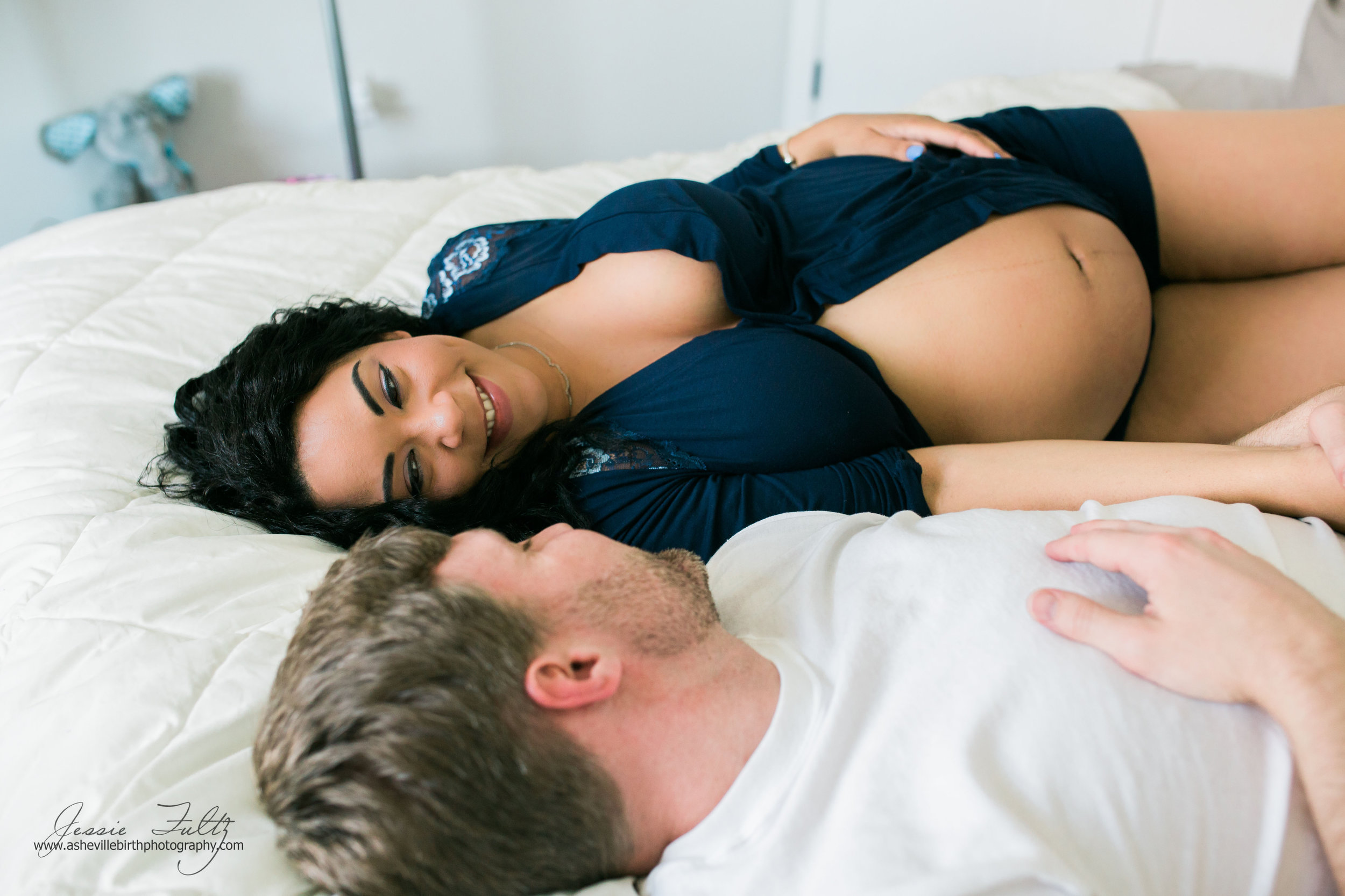 pregnant woman laying on her bed smiling while looking at her husband