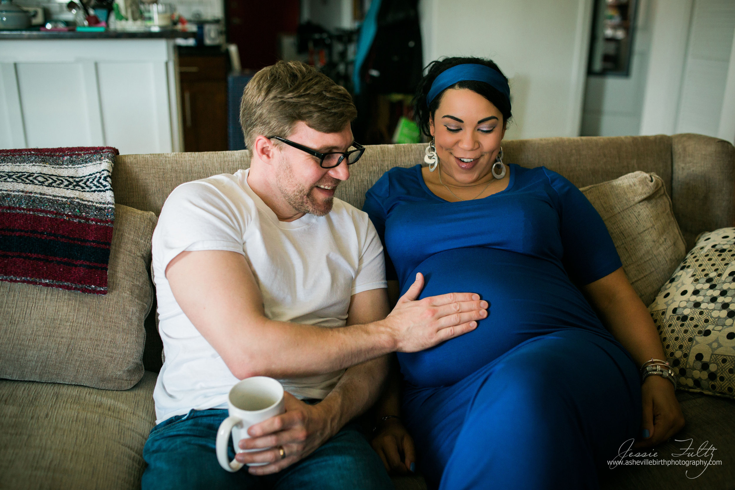 Pregnant woman in a blue dress sitting on the couch while her husband rubs her belly