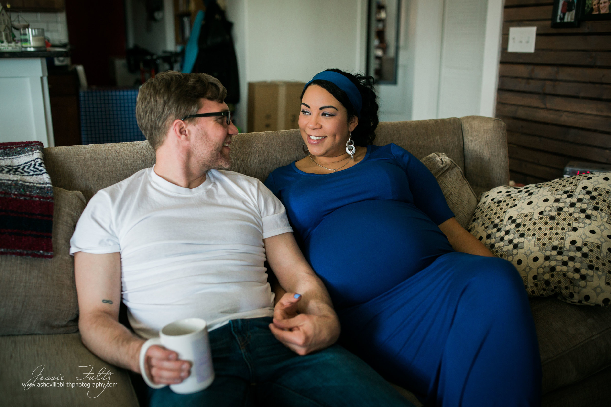 pregnant woman in blue dress and husband sitting on couch holding hands and smiling at each other