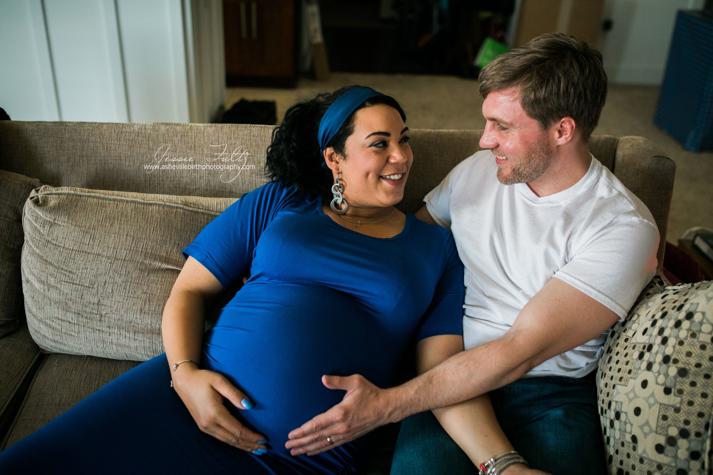 pregnant woman in a blue dress sitting on the couch smiling at her husband while he touches her belly