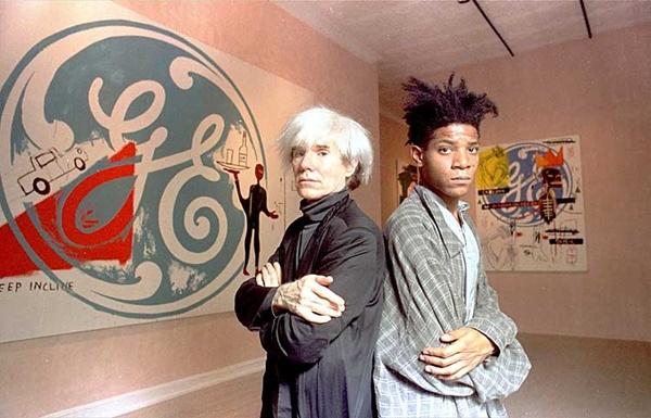 Andy Warhol y Jean-Michel Basquiat en los 1980s, durante la época que los dos famosos artistas combinaron su estrellato para vender sus obras. En esta época, Warhol no lograba vender de la misma manera como lo hacía en los años 1960s. Por lo tanto, recurrió a su amigo y protegido, Basquiat, para que éste lo ayude.