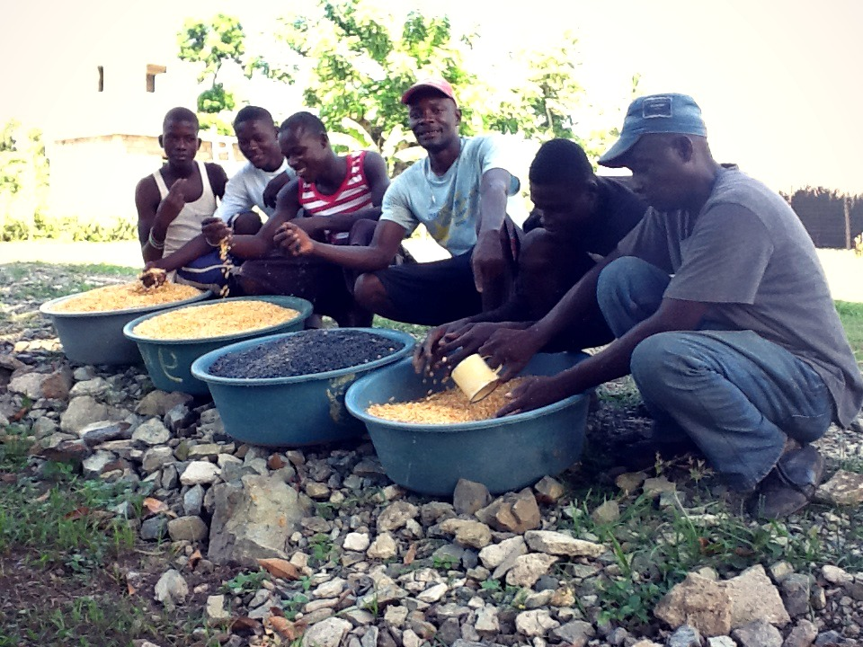 Joseph with employees showing off a recent corn and bean harvest