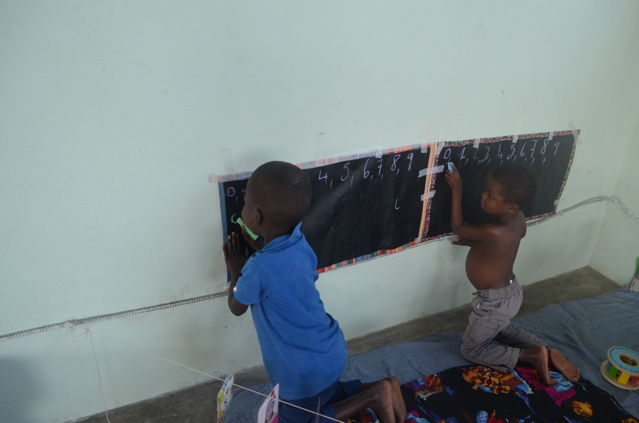 Kely (8) and Jameson (6) practice their school lessons while recovering from Severe Acute Malnutrition at Second Mile Haiti