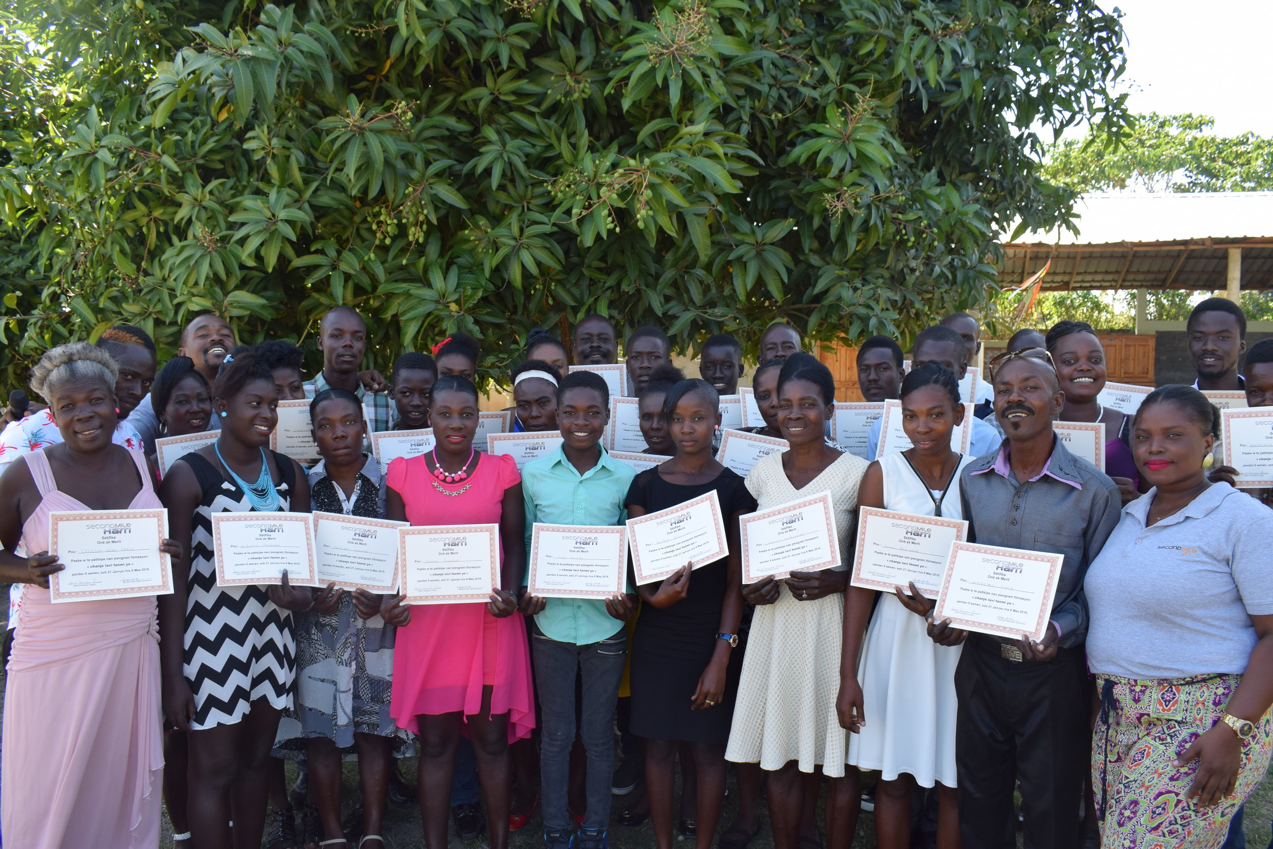 Graduates of the 7th Community Education cohort display their certificates of completion