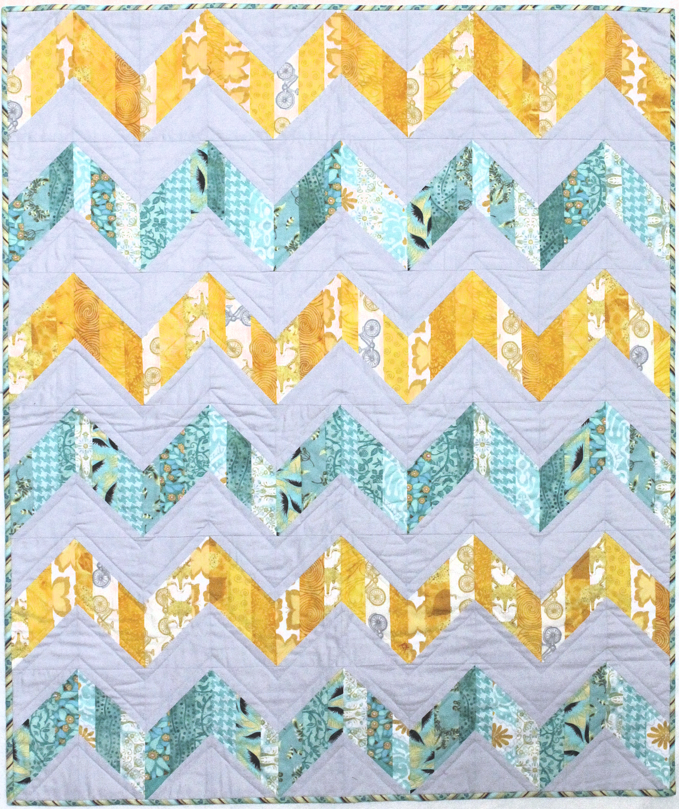 The original quilt used light gray and modern fabrics in teal and yellow