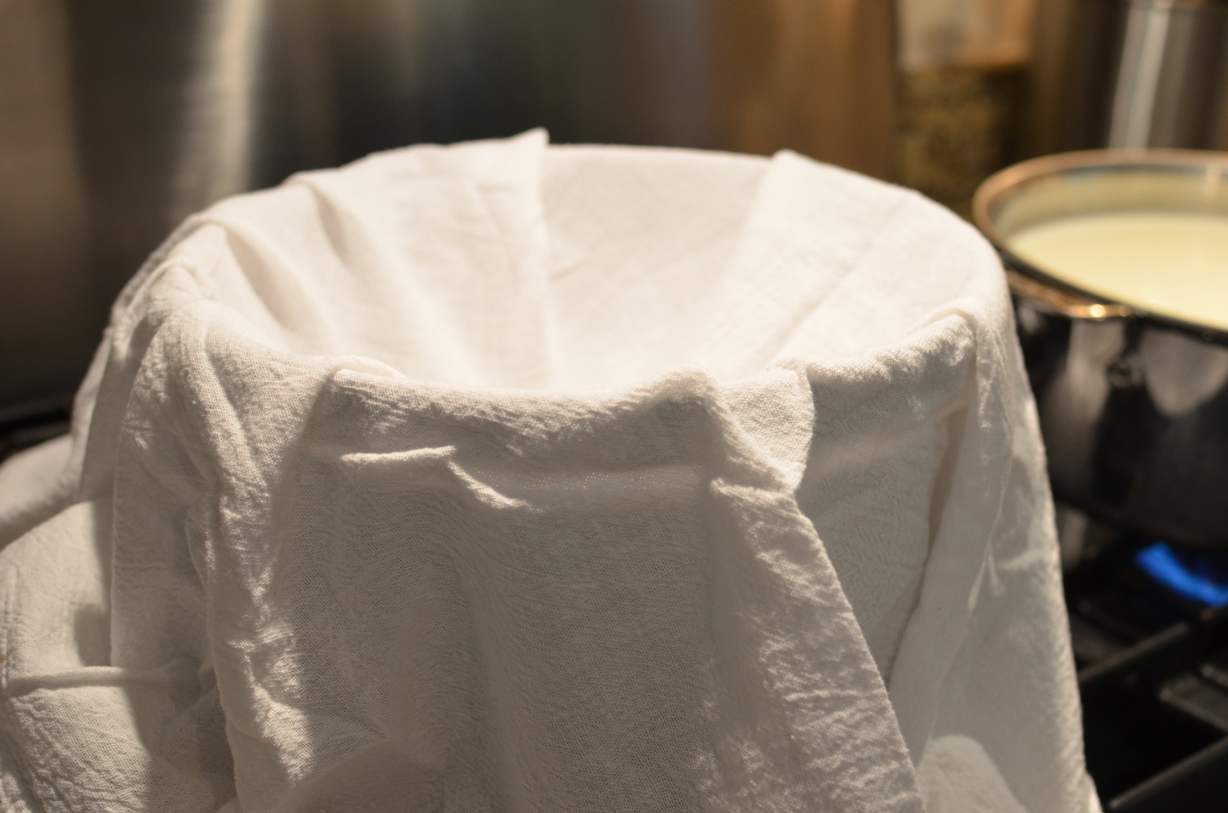 Line the sieve with a very clean tea towel. You could use a few layers of cheesecloth is you like, but a linen tea towel works perfectly well.