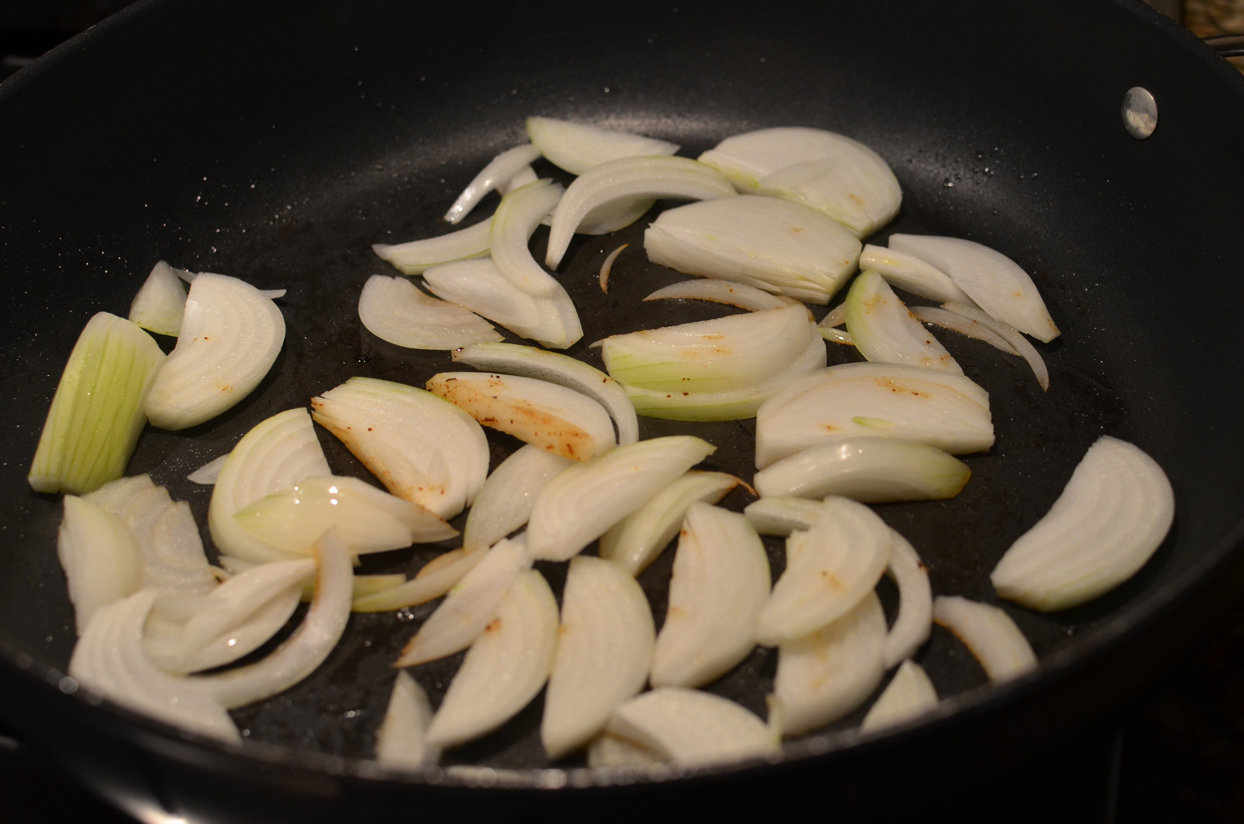 In the same pan, saute the sliced onions in the rendered kielbasa fat.