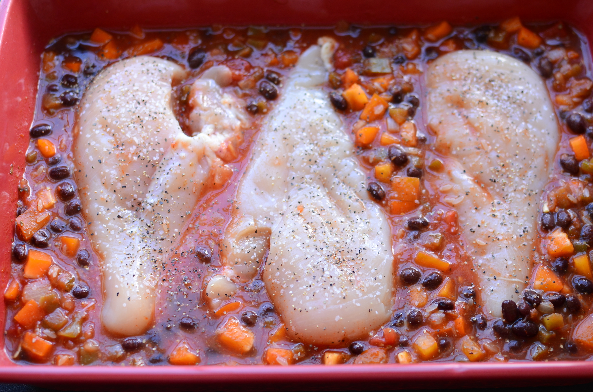 Now nestle the chicken breasts down into the mixture. No need to bury the chicken in the mixture. Be sure to sprinkle kosher salt and ground black pepper on that chicken!