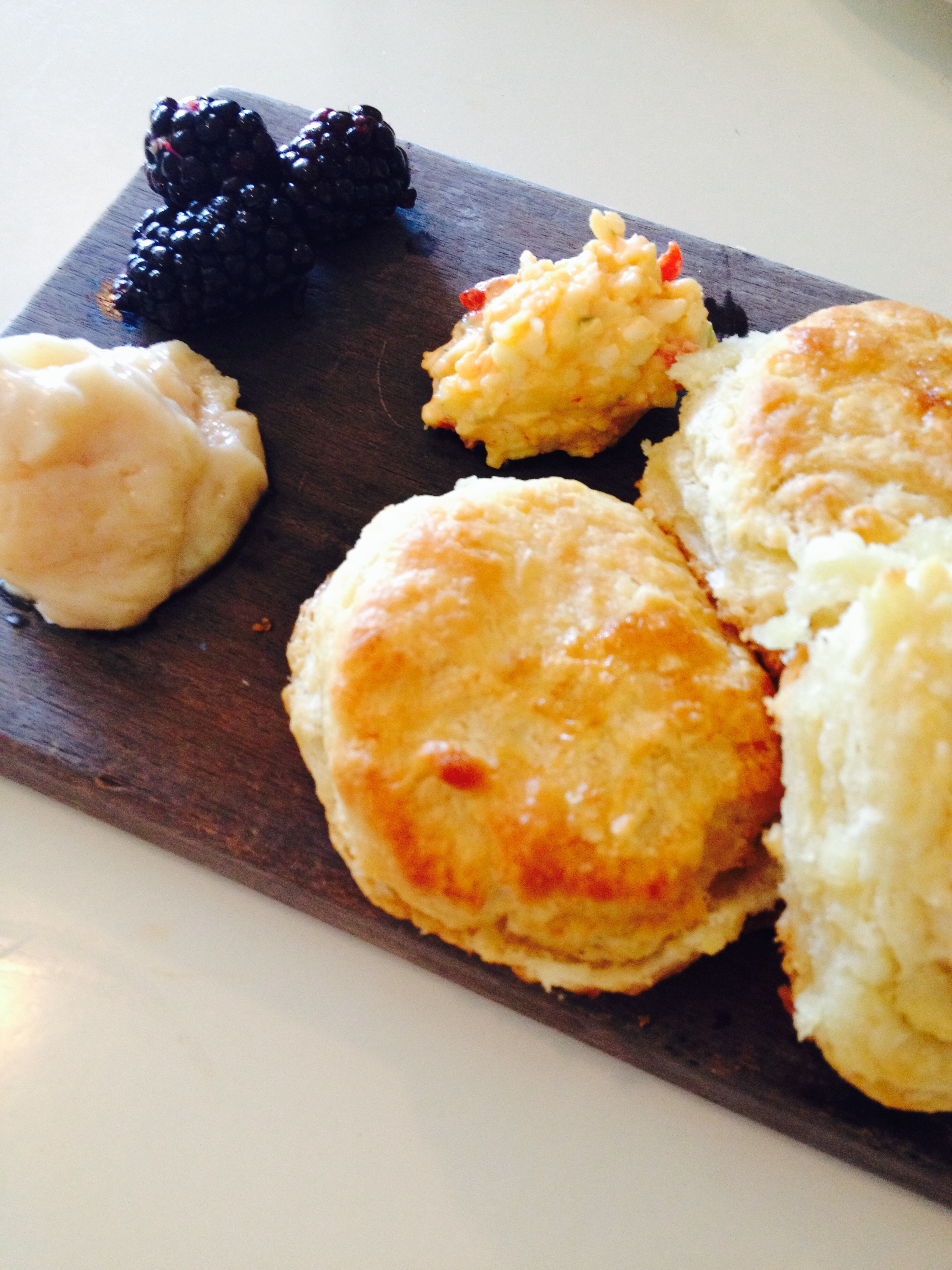 Butter biscuits with pimento cheese, honey butter, and blackberries.