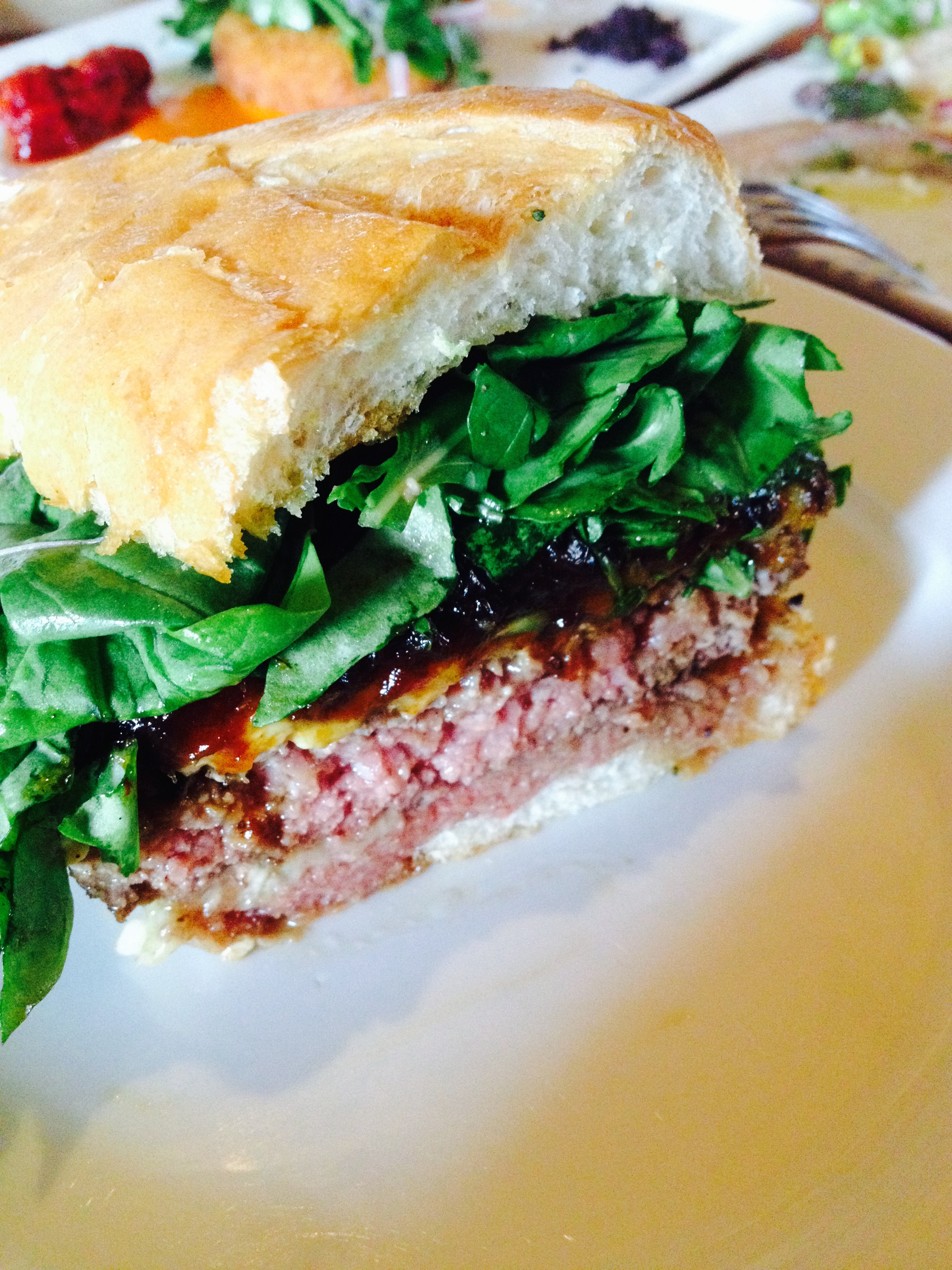The Office Burger ®  with dry-aged beef, caramelized onions, bacon, gruyère, Maytag blue cheese, and arugula.