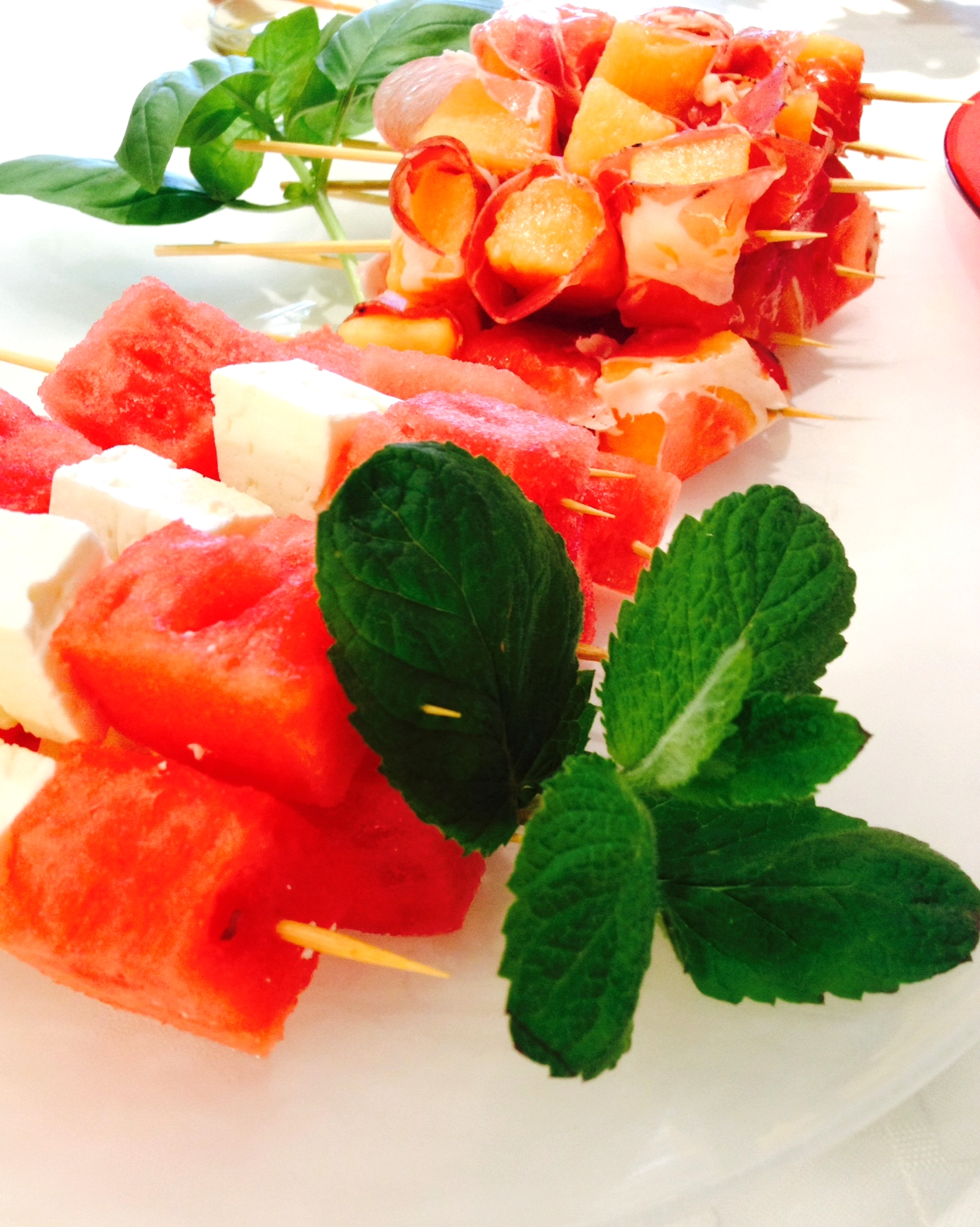 (front) Watermelon and Feta Cheese Skewers with Mint (back) C antelope and Prosciutto Skewers with Basil