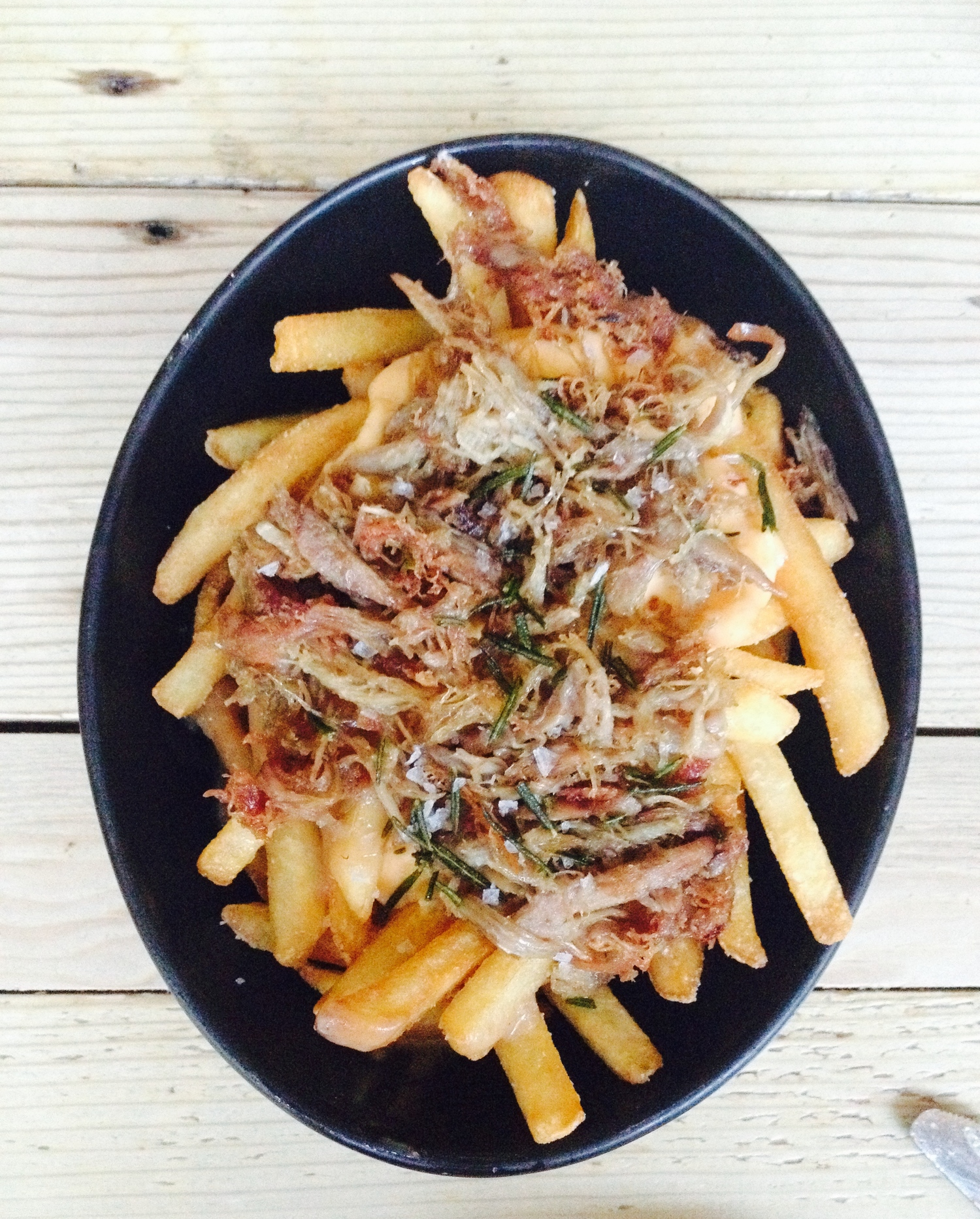 Duck confit poutine with gravy, cheddar mornay, and fried rosemary