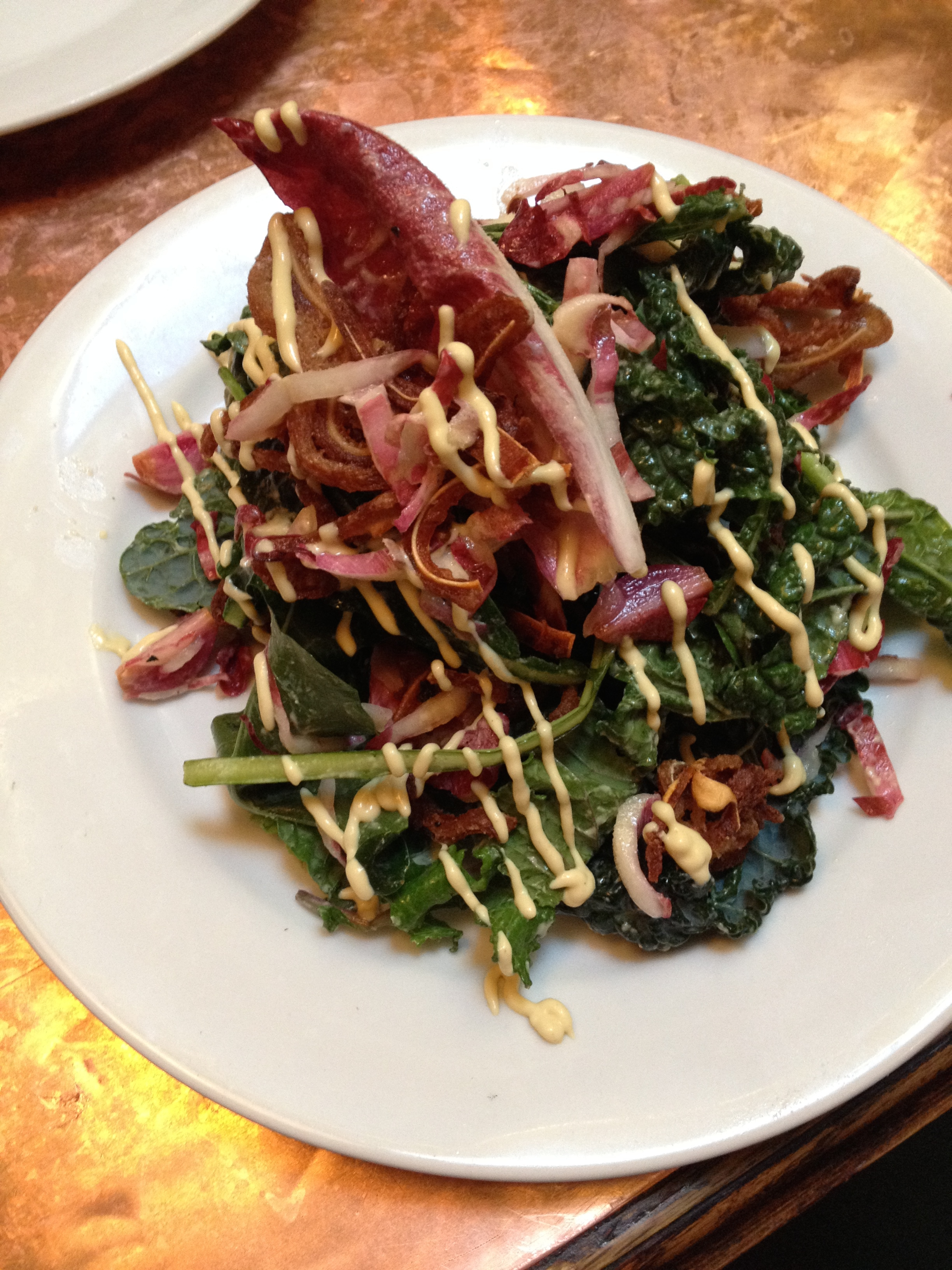 Crispy Pig's Ear Salad with young kale, endive, pickled onions, and mustard dressing