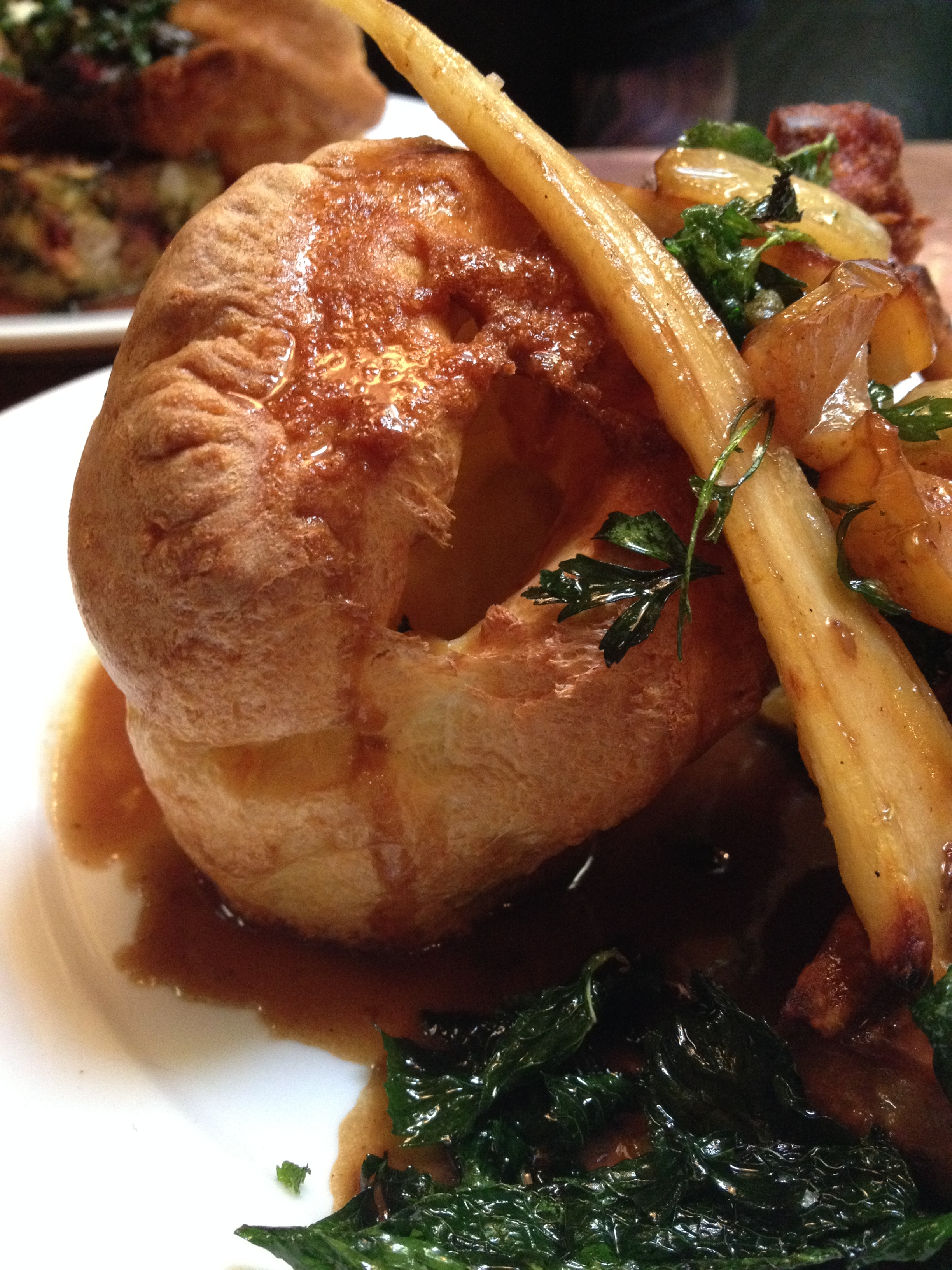 Sunday Roast Slow-Roasted Pork Belly with Caramelized Apples & Parsnips, accompanied by stuffing, roasted potatoes, Yorkshire pudding, and gravy.