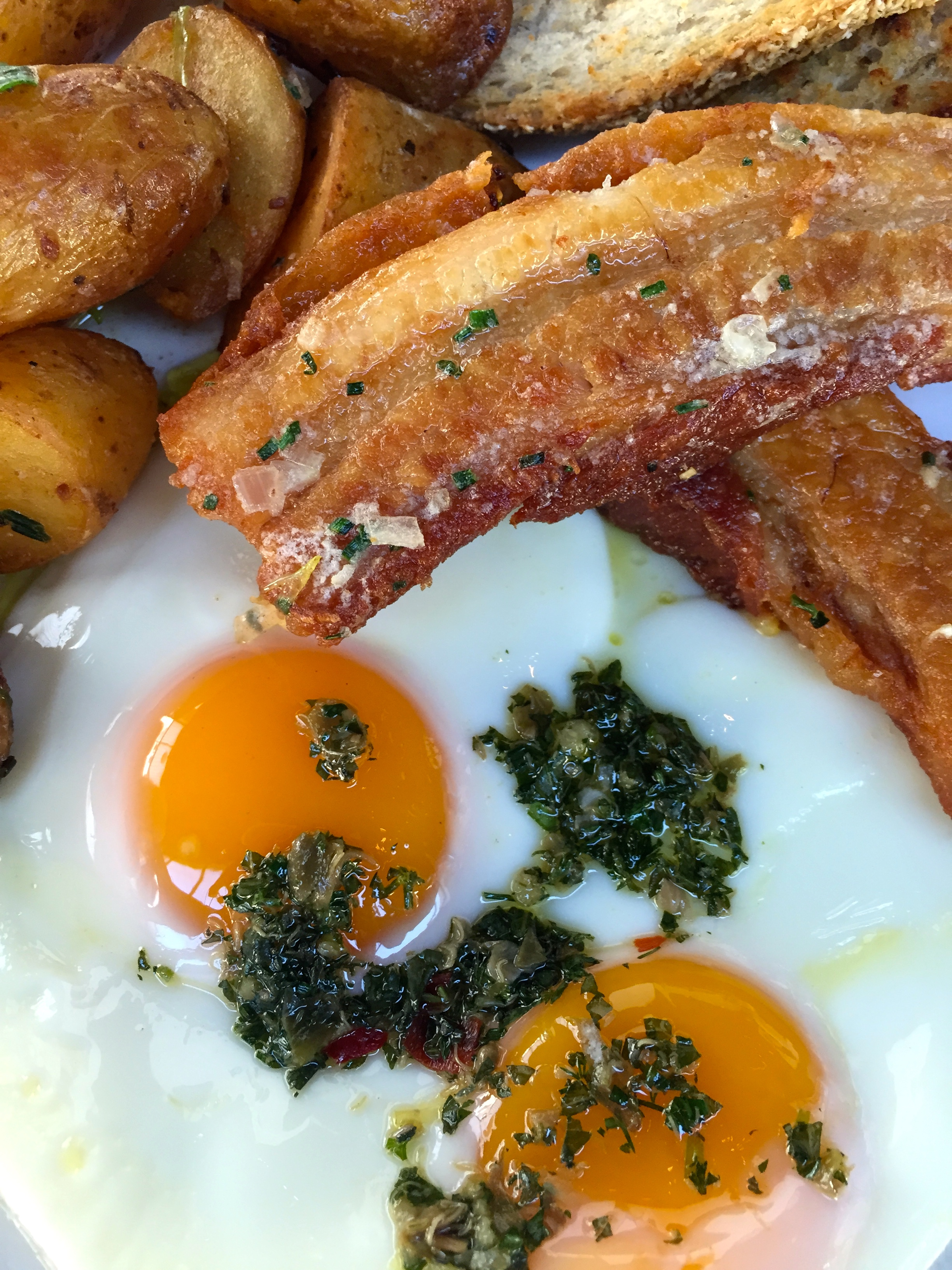 Breakfast Combo with fried eggs, duck fat potatoes, crispy pork belly, and salsa verde.