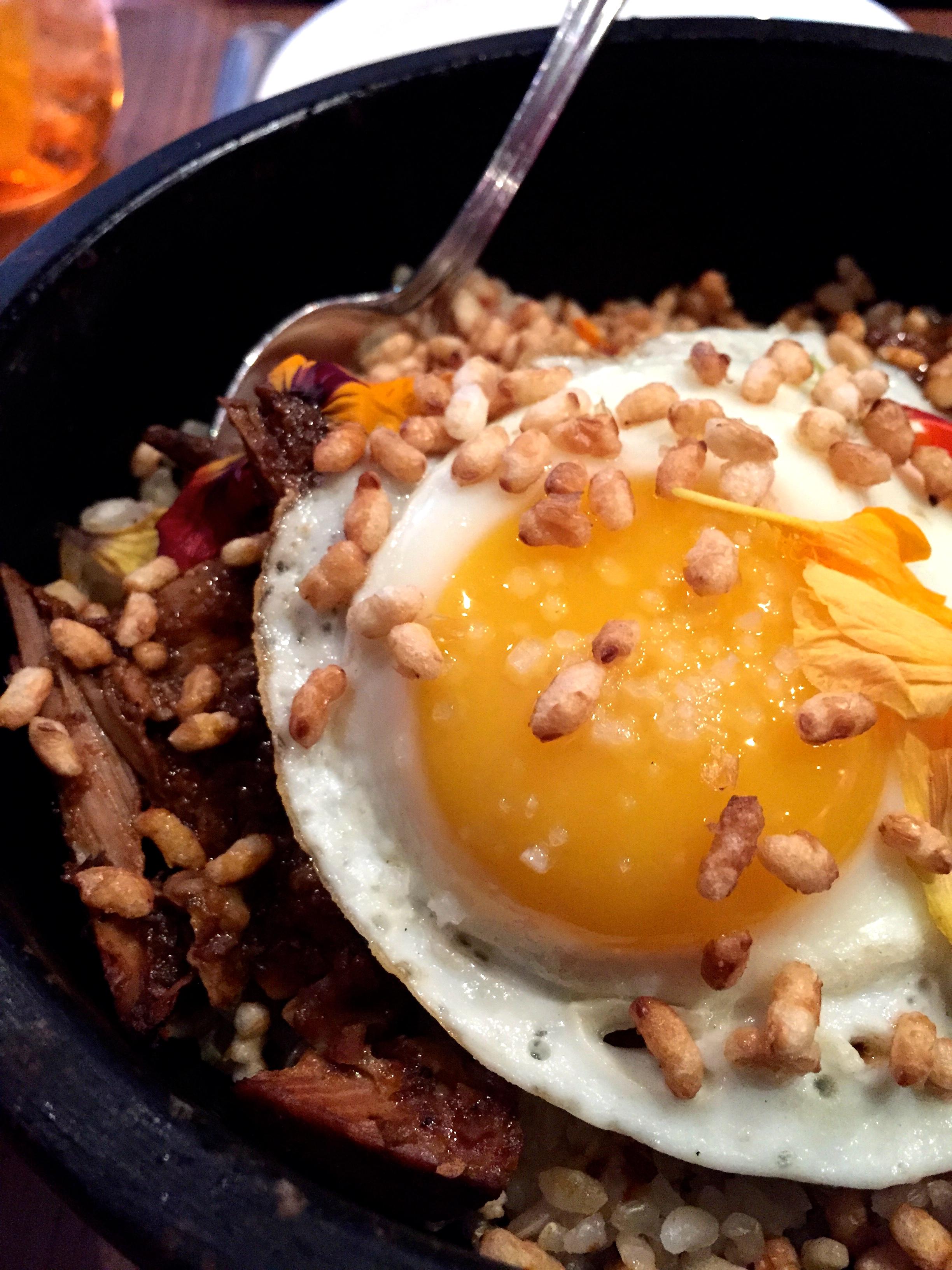 Romesco Braised Pork Belly with crispy satsuki rice, charred leek, and afried egg.