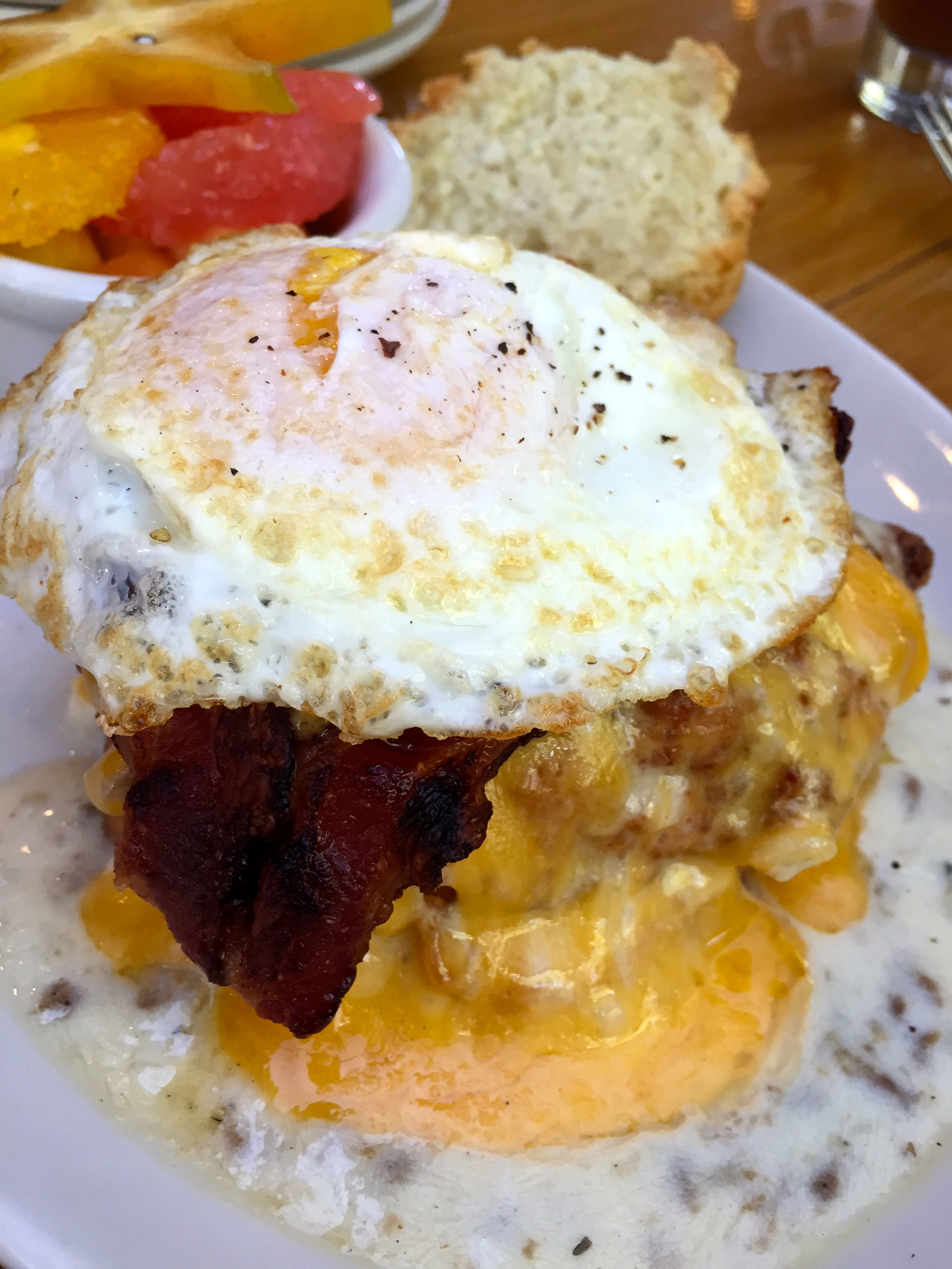 SxSW fried chicken, country gravy, bacon, cheddar, egg on a biscuit served with fruit.