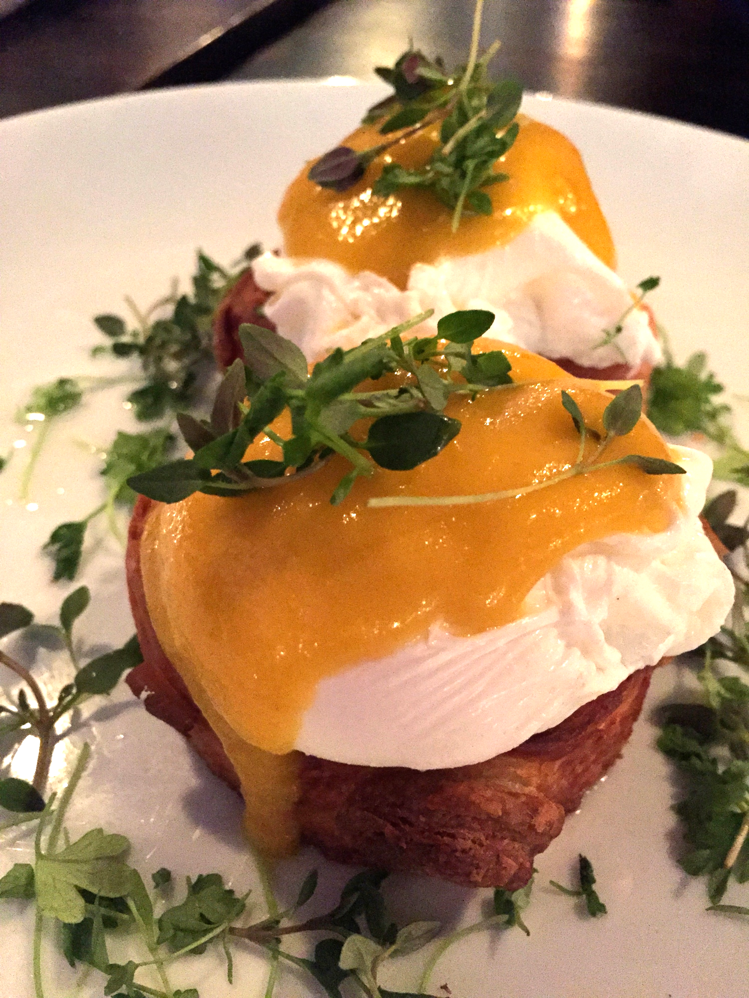 Benedict and Cumberland, two slices of our Cumberland roll topped with two poached organic pastured eggs, yellow tomato béarnaise surrounded by an herb salad.