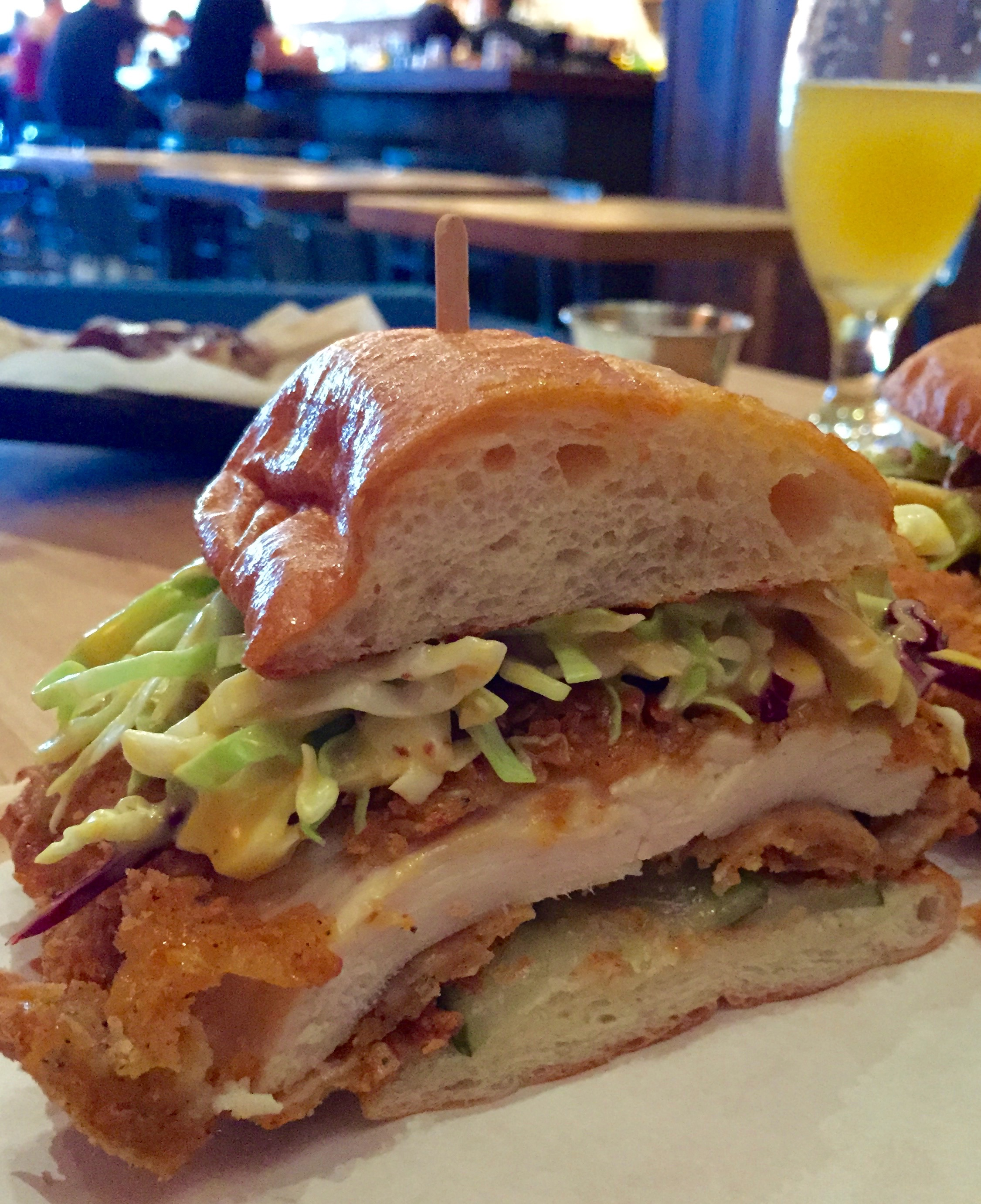 Crispy Chicken Sandwich with chicken breast, cabbage slaw, dill pickles on a sweet roll.