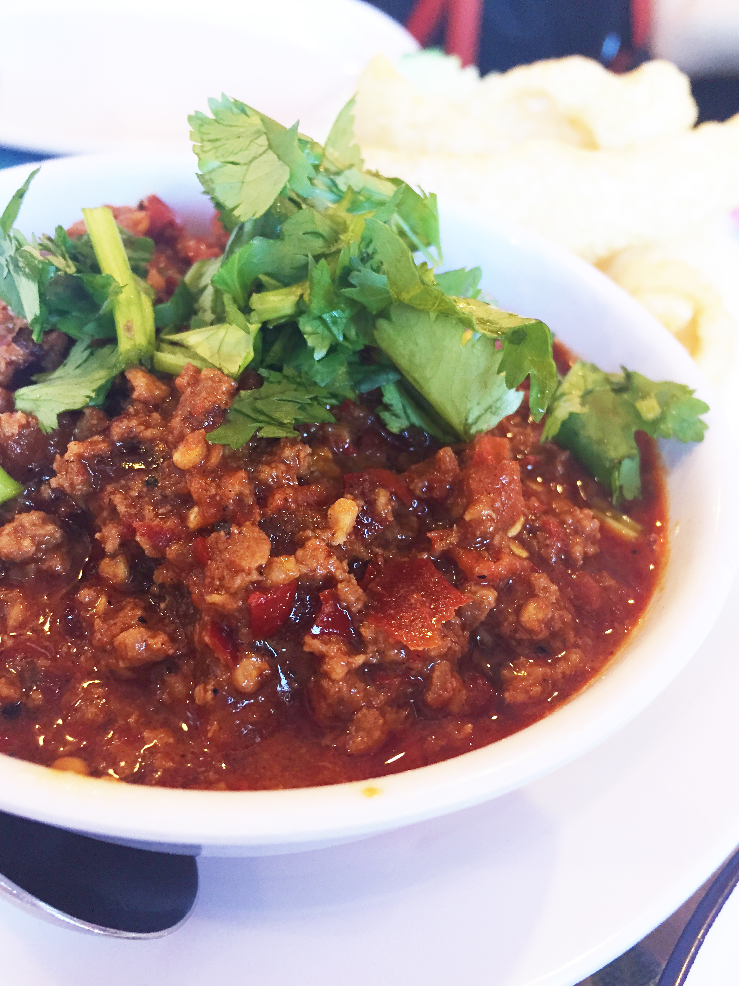 """Nam Prik Ong -a homemade ground pork """"ragout""""cooked down withgapi, cherry tomatoes, androasted chile, served withpork rinds."""