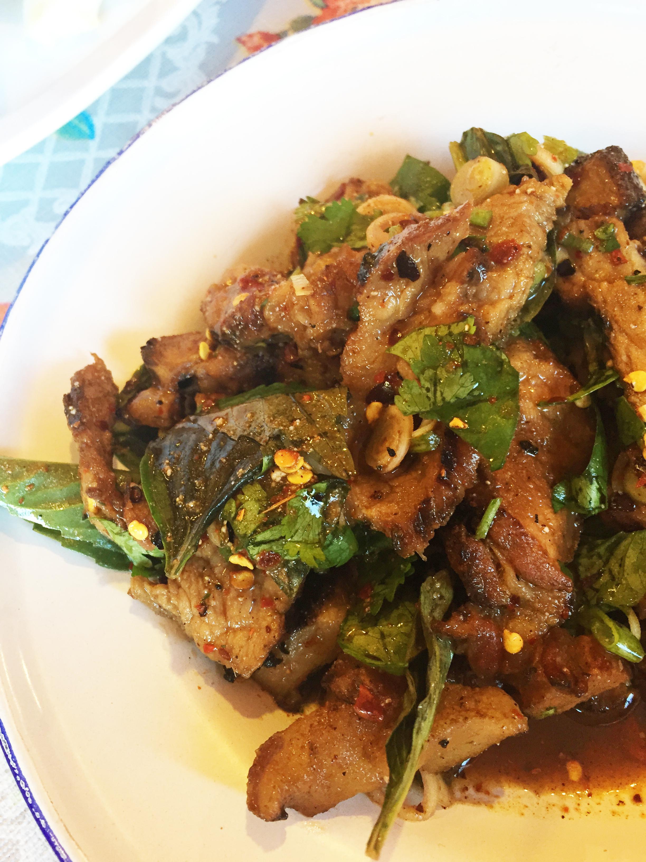"Moo Sadoong ""Startled Pig"" -grilled pork, basil, lemongrass, garlic, fish sauce, lime, chile, onions, cilantro, and rice powder."
