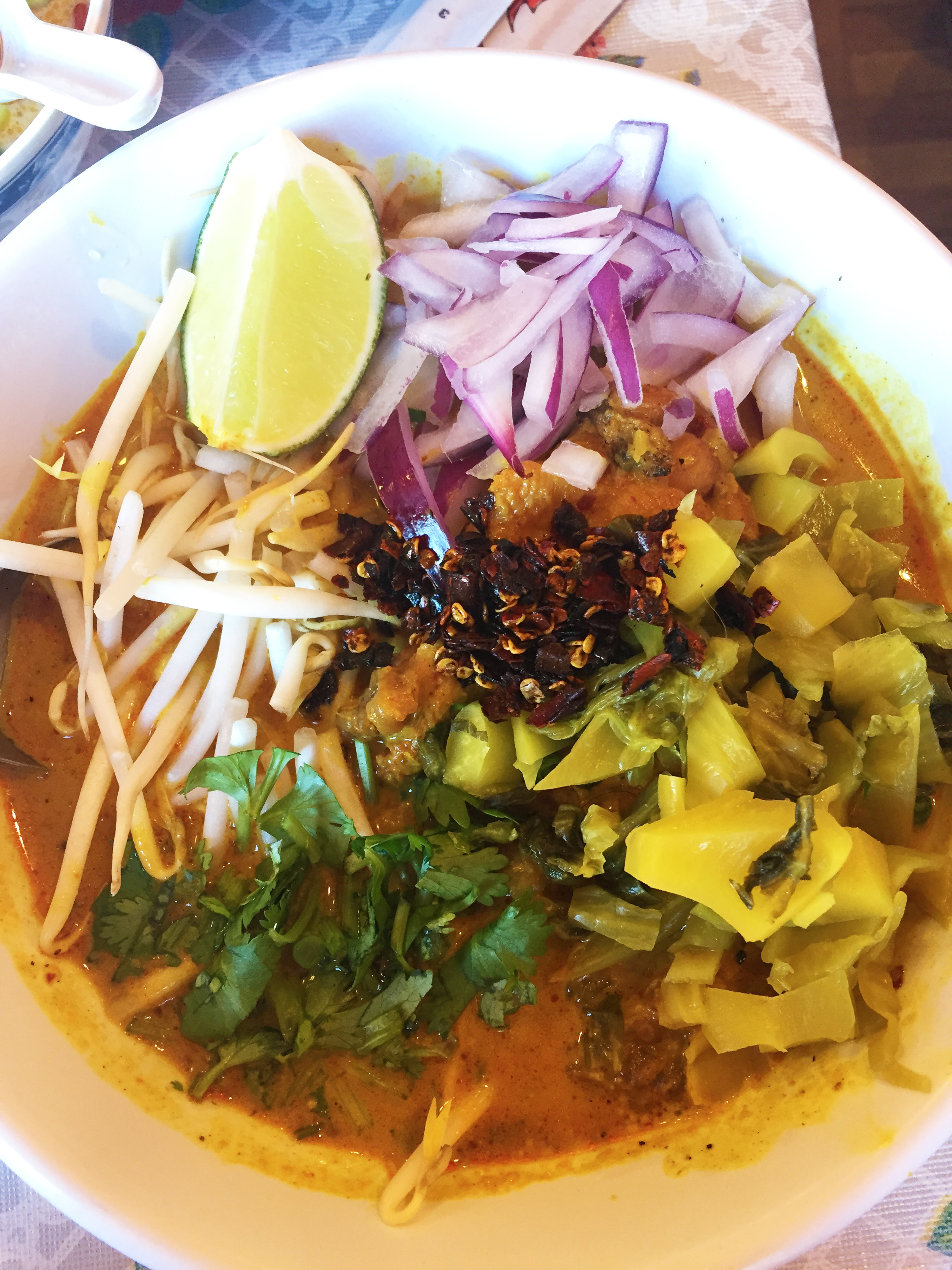 Khao Soi Gai -mae sai curried noodles withchicken andhomemade nam prik khao soi,topped withbean sprouts, red onion, pickled mustard greens, cilantro, andchile jam.