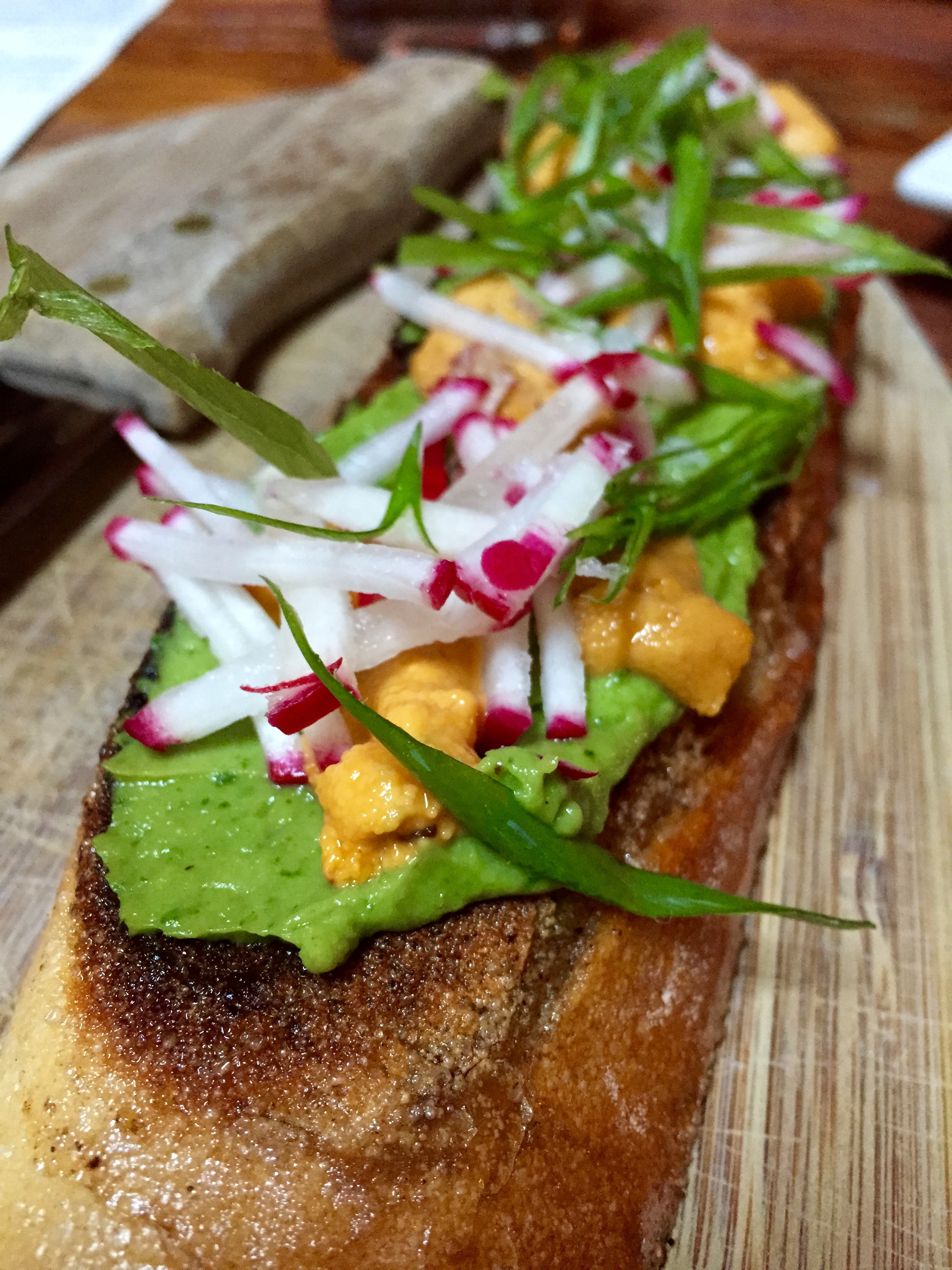 Sea Urchin Toast with avocado mousse, radish, and scallions.