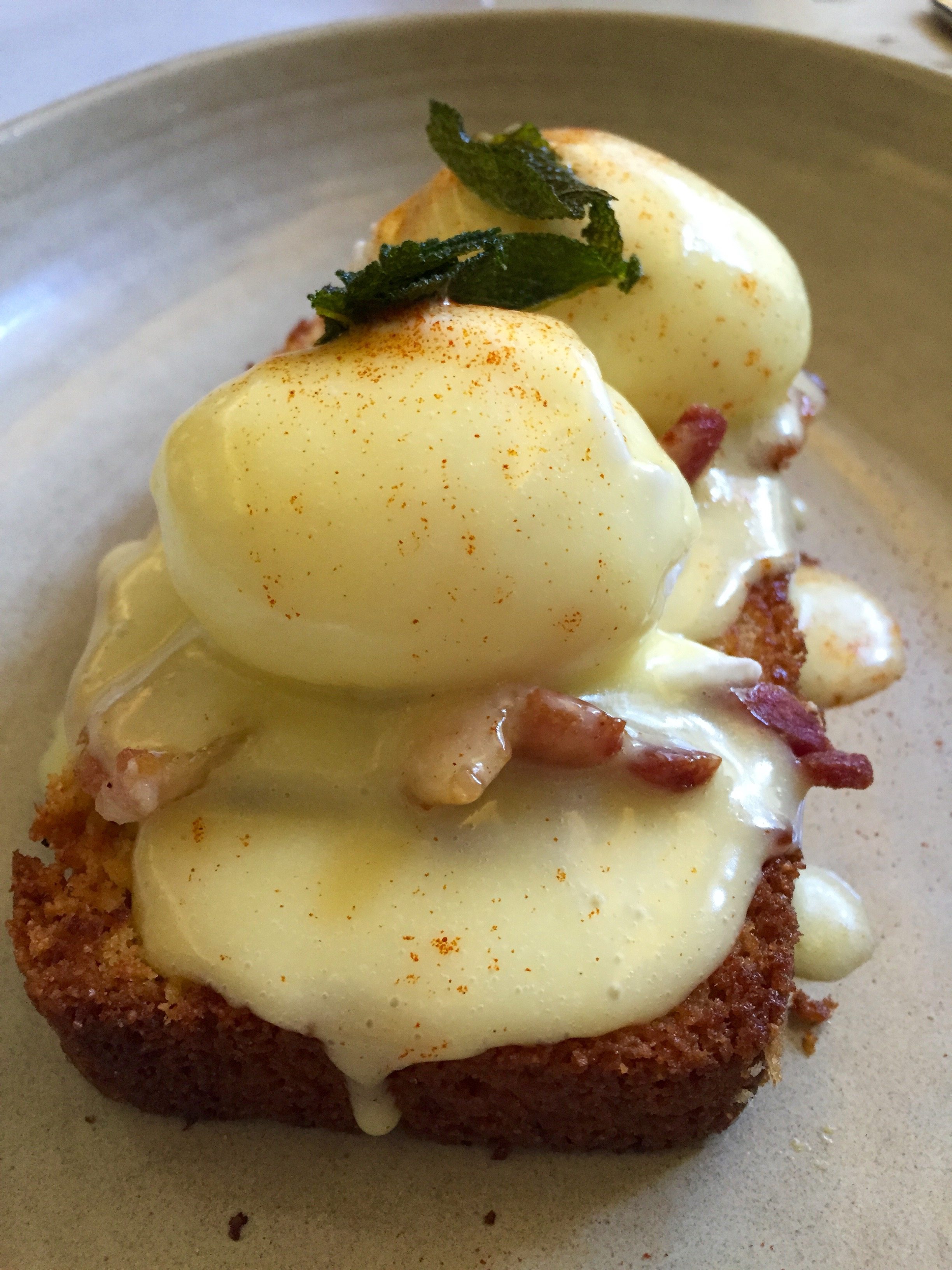 Smoked Pork Belly Benedict on corn bread with poached eggs and pimento hollandaise.