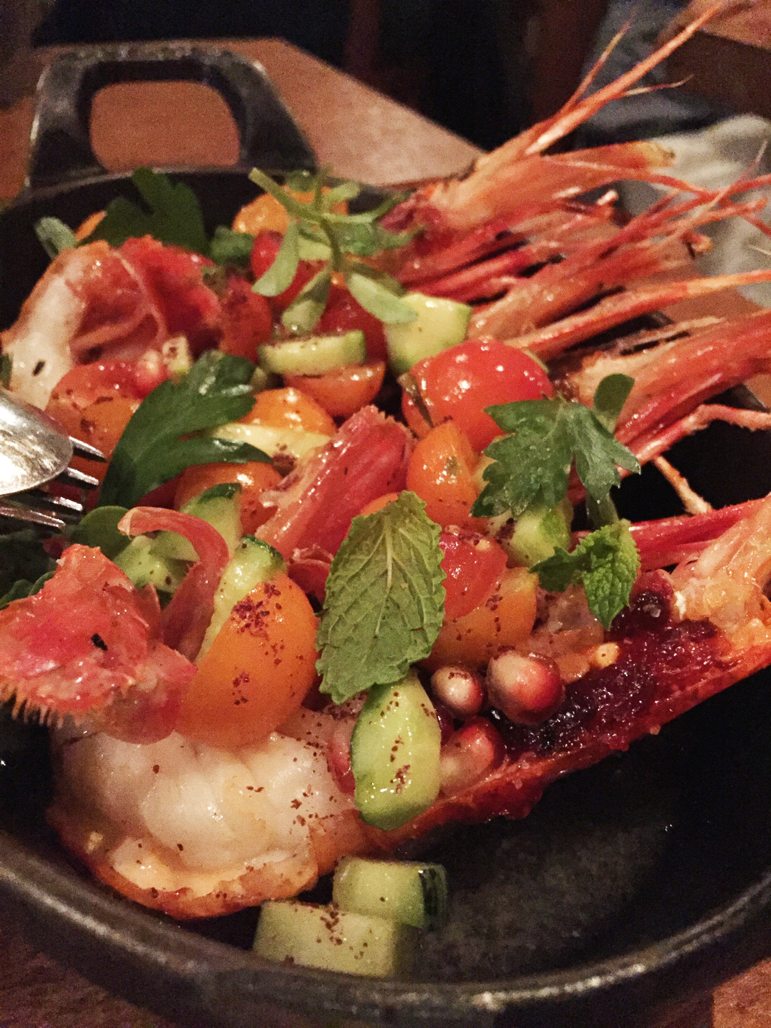 Grilled Santa Barbara Prawns with charred eggplant, cherry tomatoes, cucumbers, and sumac.