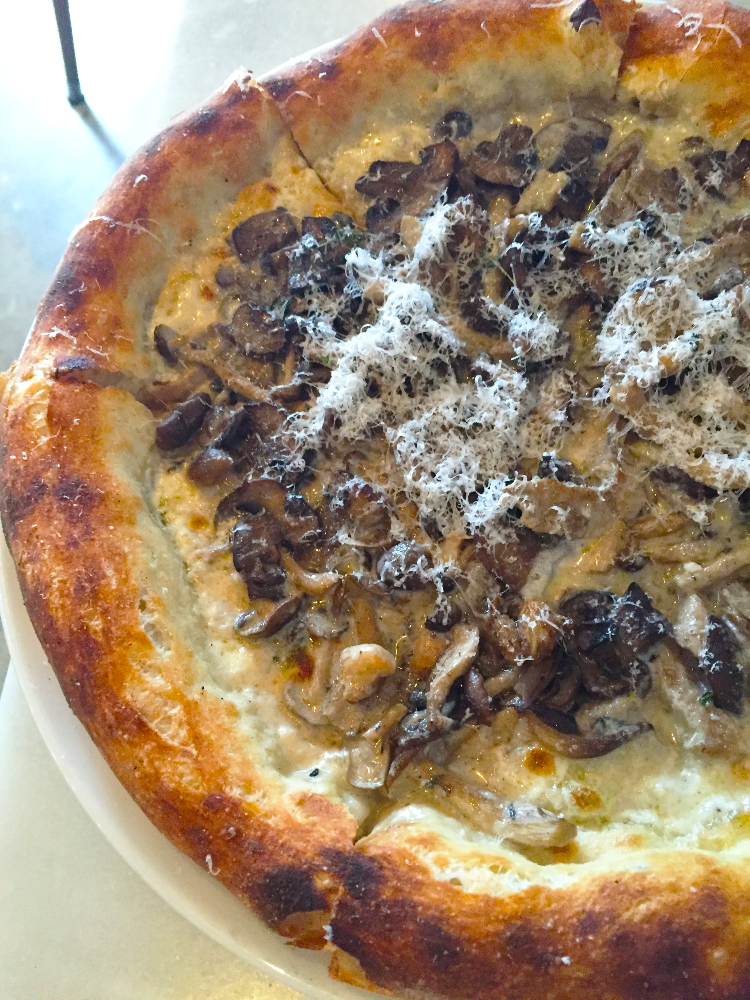 Mixed Mushroom Pizza with fontina val d'aosta, thyme, lemon zest, and parmesan.