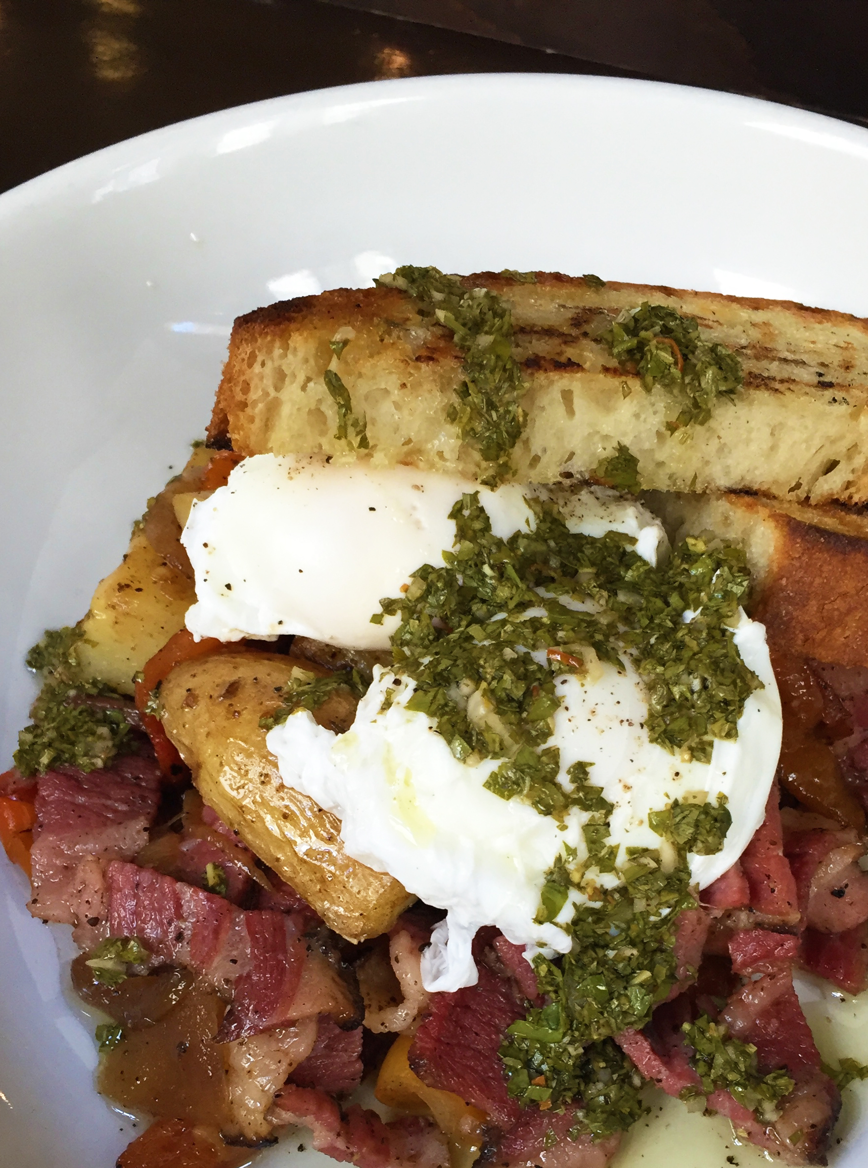 Pastrami Hash with fingerling potatoes, caramelized onions, peppers, roasted squash, salsa verde, and poached eggs.