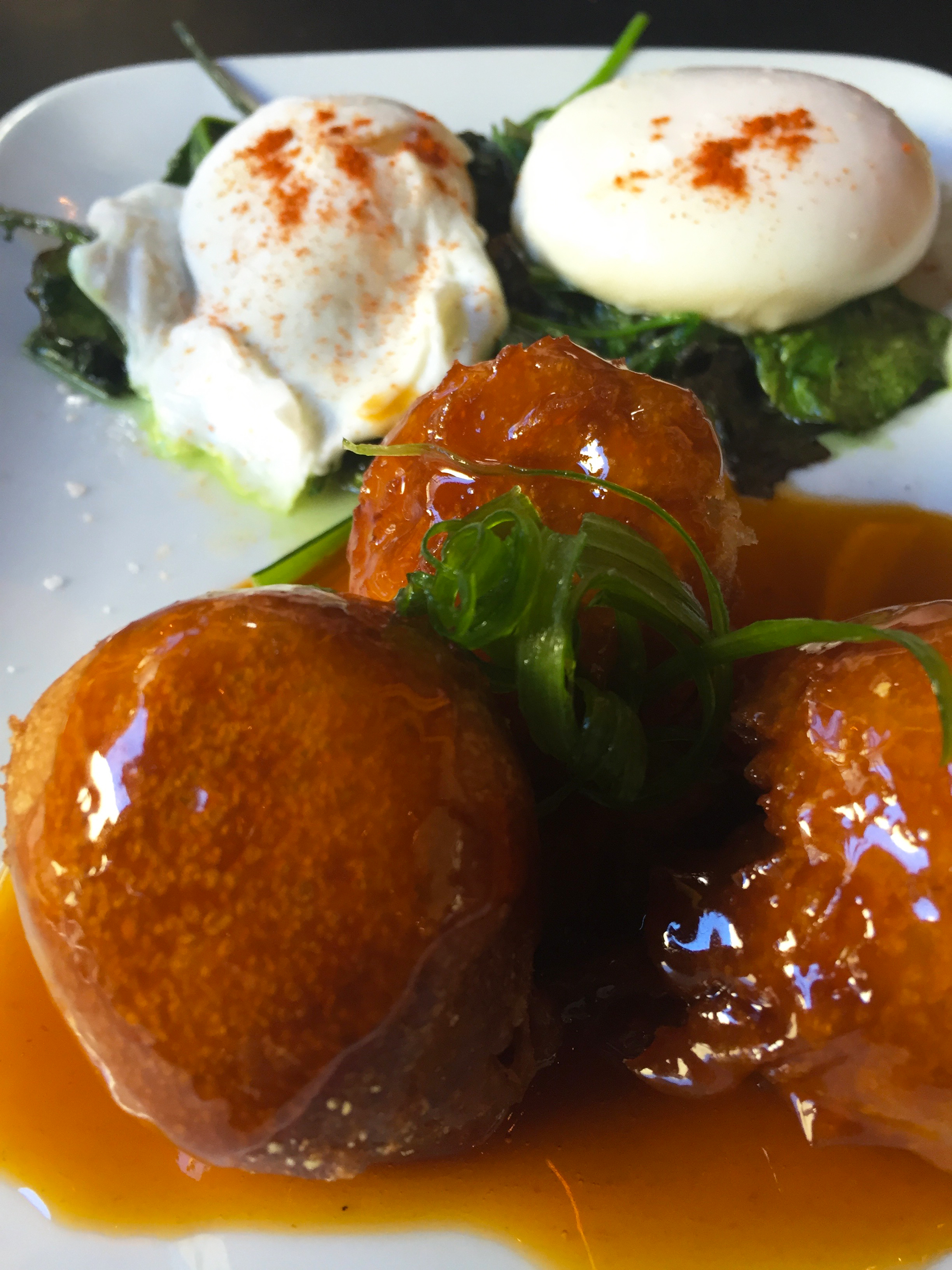 Chicken and Waffle Croquettes with bacon, spicy maple sauce, braised greens and slow cooked eggs.