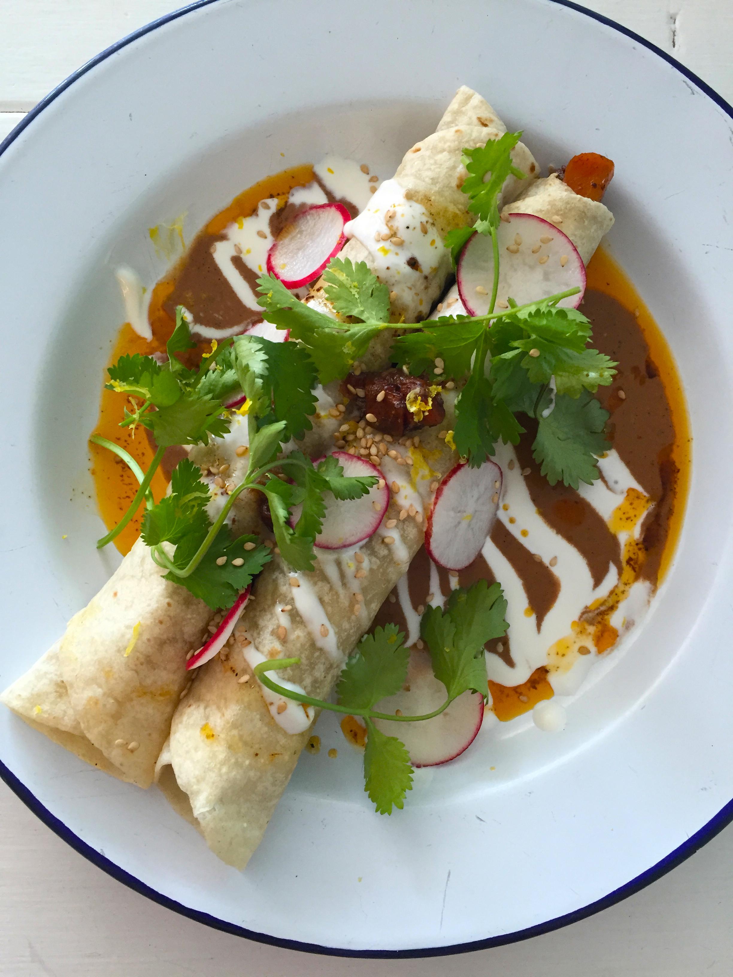 Carrot mole enchiladas with crème fraiche and cilantro.