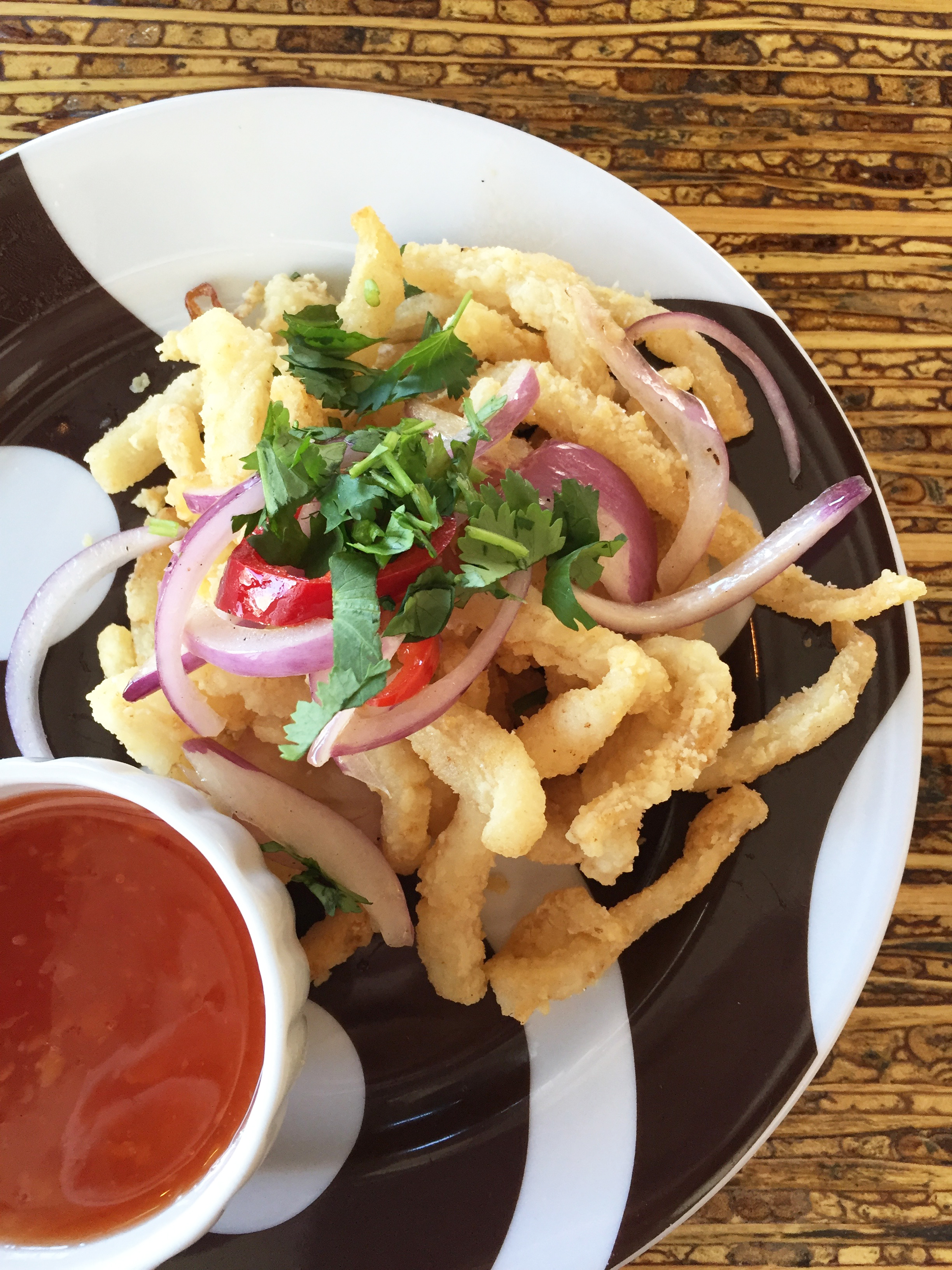 Crispy Calamari with sweet salt, pepper, grilled onion, cilantro, and chilies.