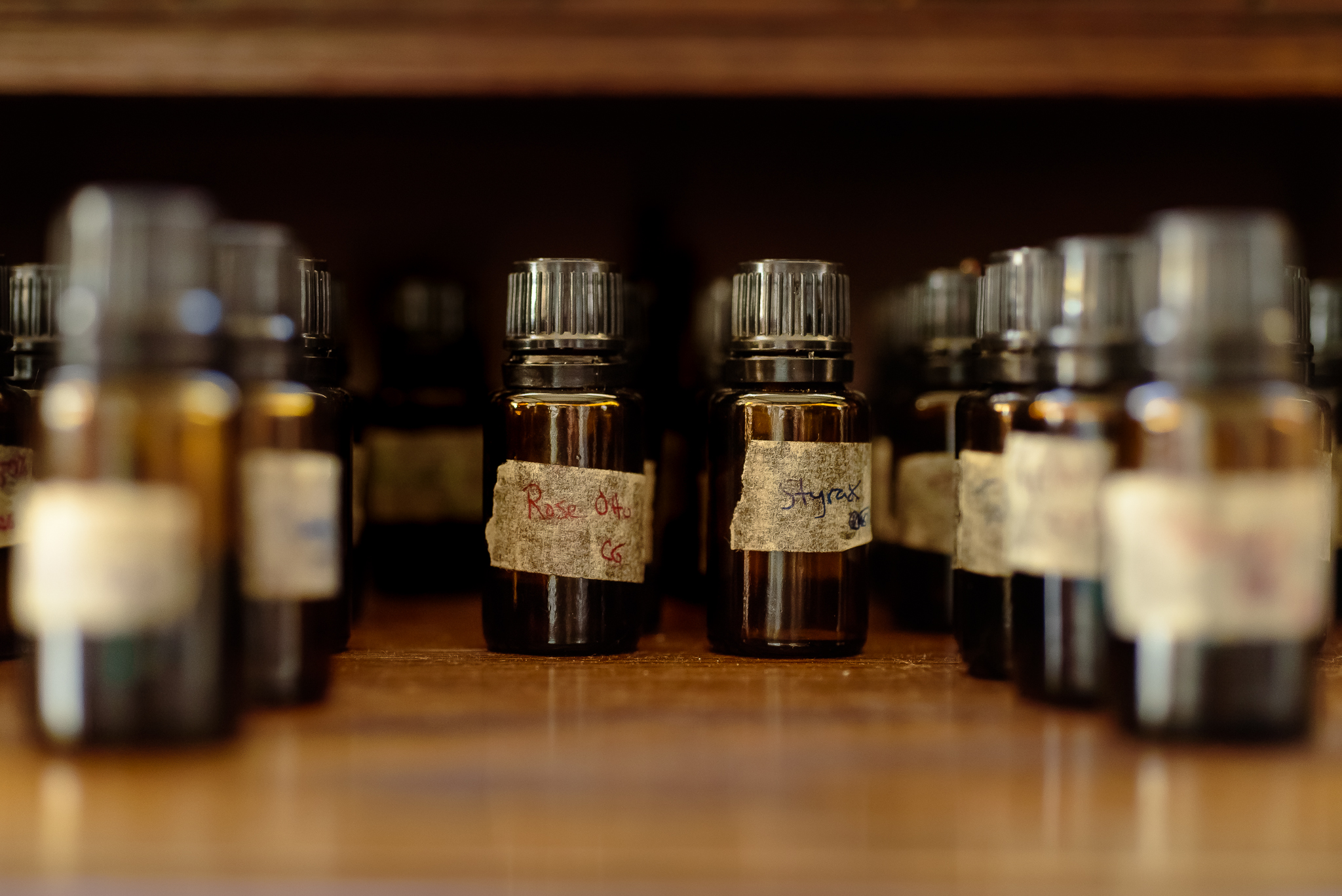 Countless essential oil vials line the shelves of Kevin's workspace.