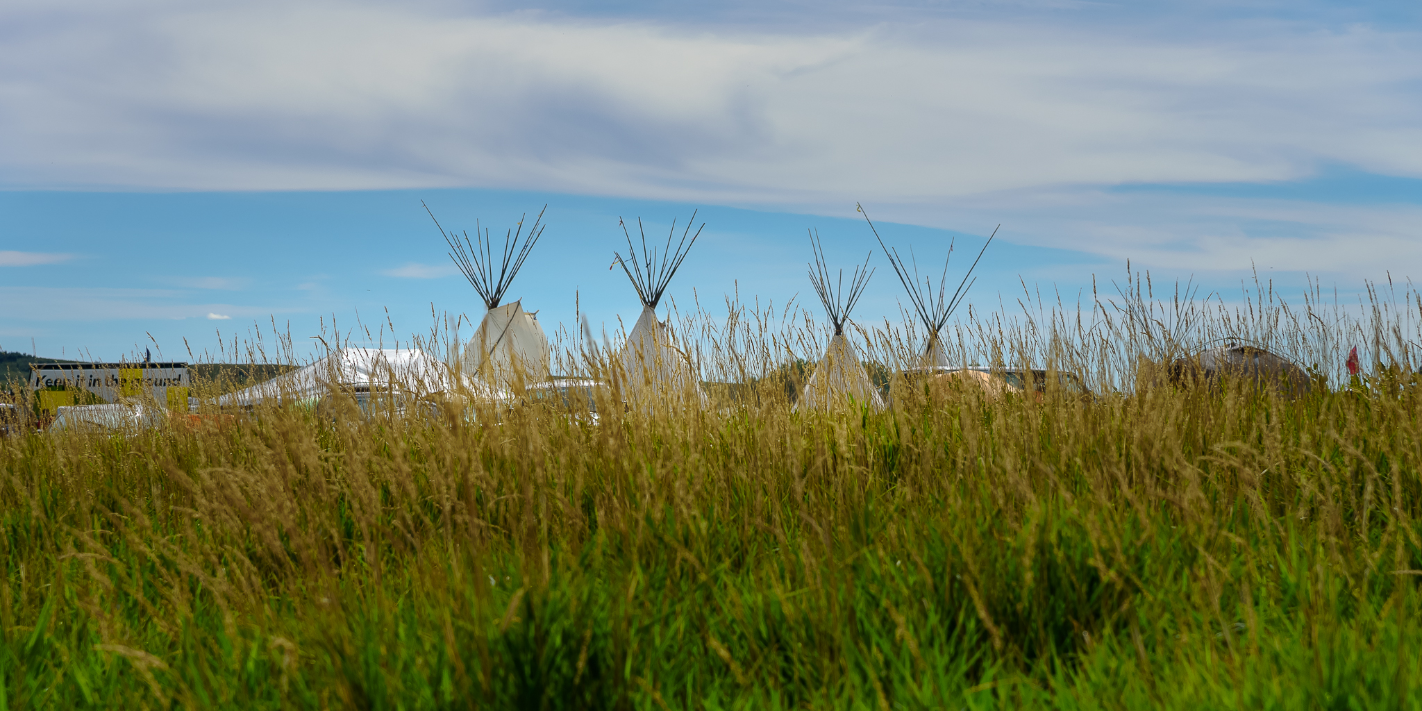 Teepees sprouted from the ground as effortlessly as the tall grass surrounding them. Standing Rock Reservation Area, ND.