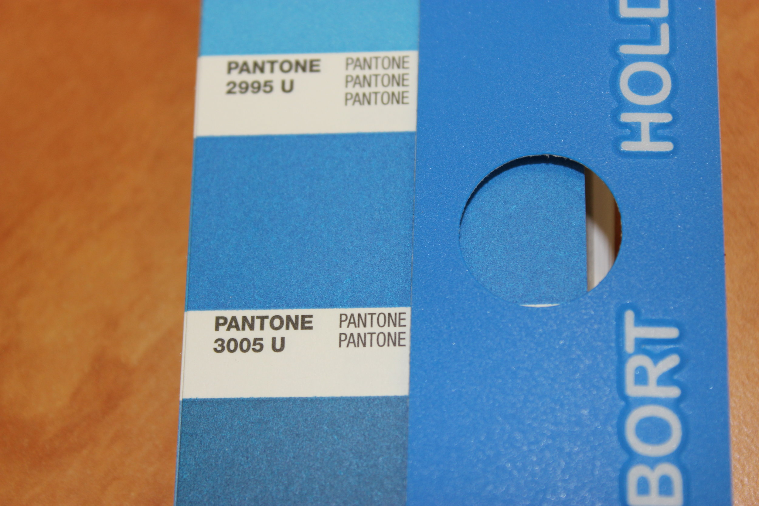 This Pantone booklet shows a matte finish, which was offset printed on paper, while the overlay uses the same color screen printed on plastic. To the trained eye, the colors are different - but still use the same formula. The cause for the difference in color: the material.