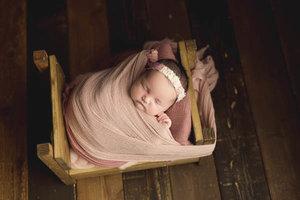Newborn girl tucked into vintage bed prop